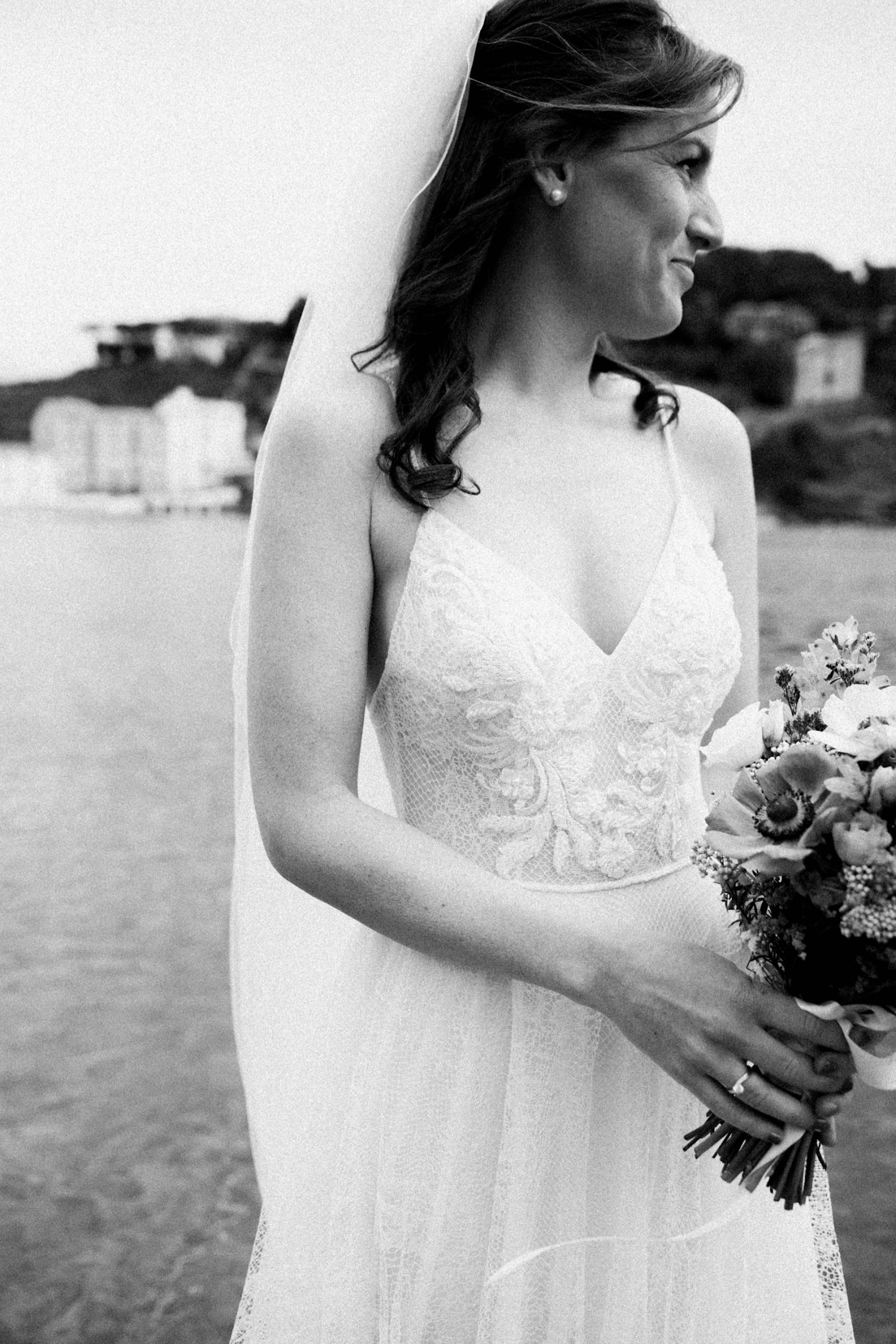 A black & white Destination Wedding of a bride holding her bouquet at the Bay of Silence in Sestri Levante on the Italian Riviera.