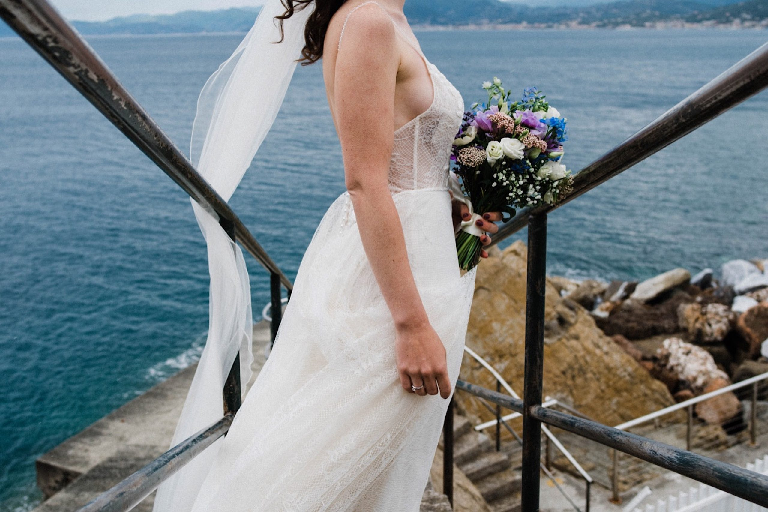 A wedding photo looking down a flight of stairs as the bride's veil flies in the wind.