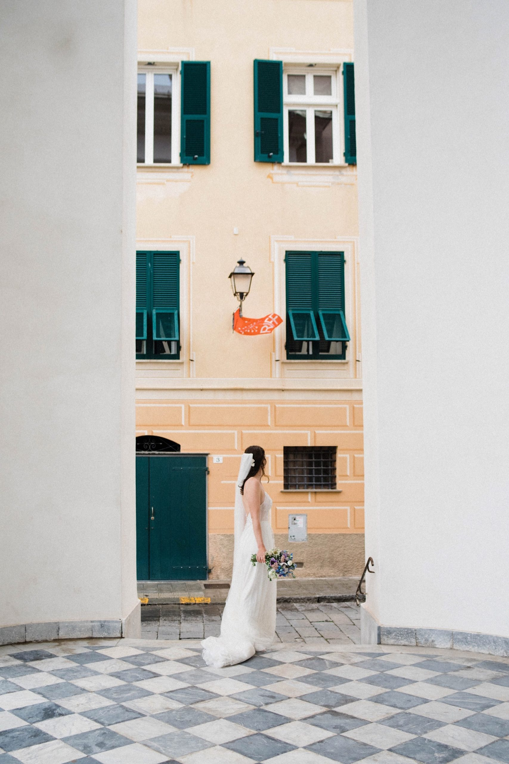 A classic wedding portrait of a bride standing on the portico of an old building in Sestri Levante.