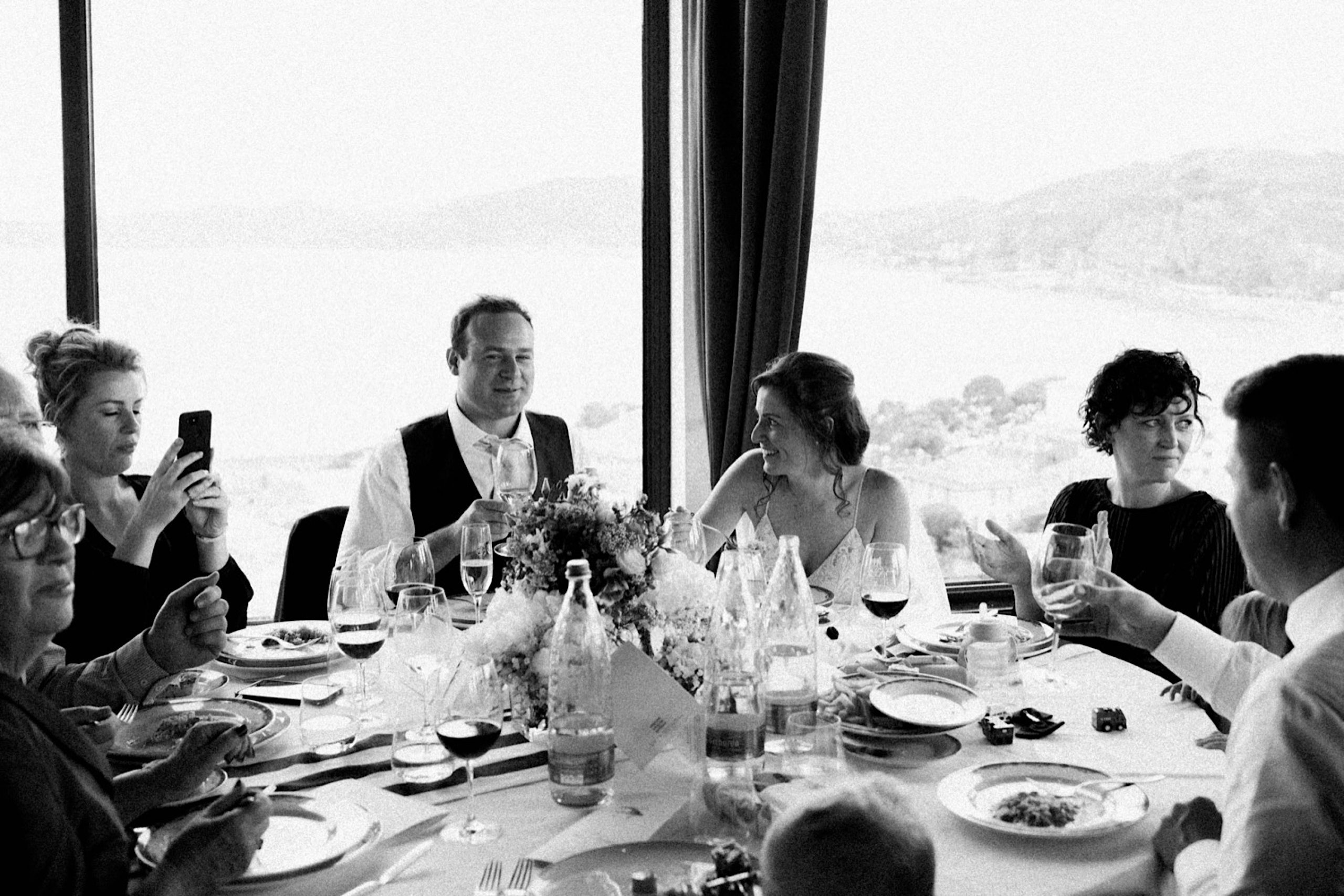 Black & White Candid Wedding Photography of a newlywed couple sitting at their Sestri Levante Wedding Reception.
