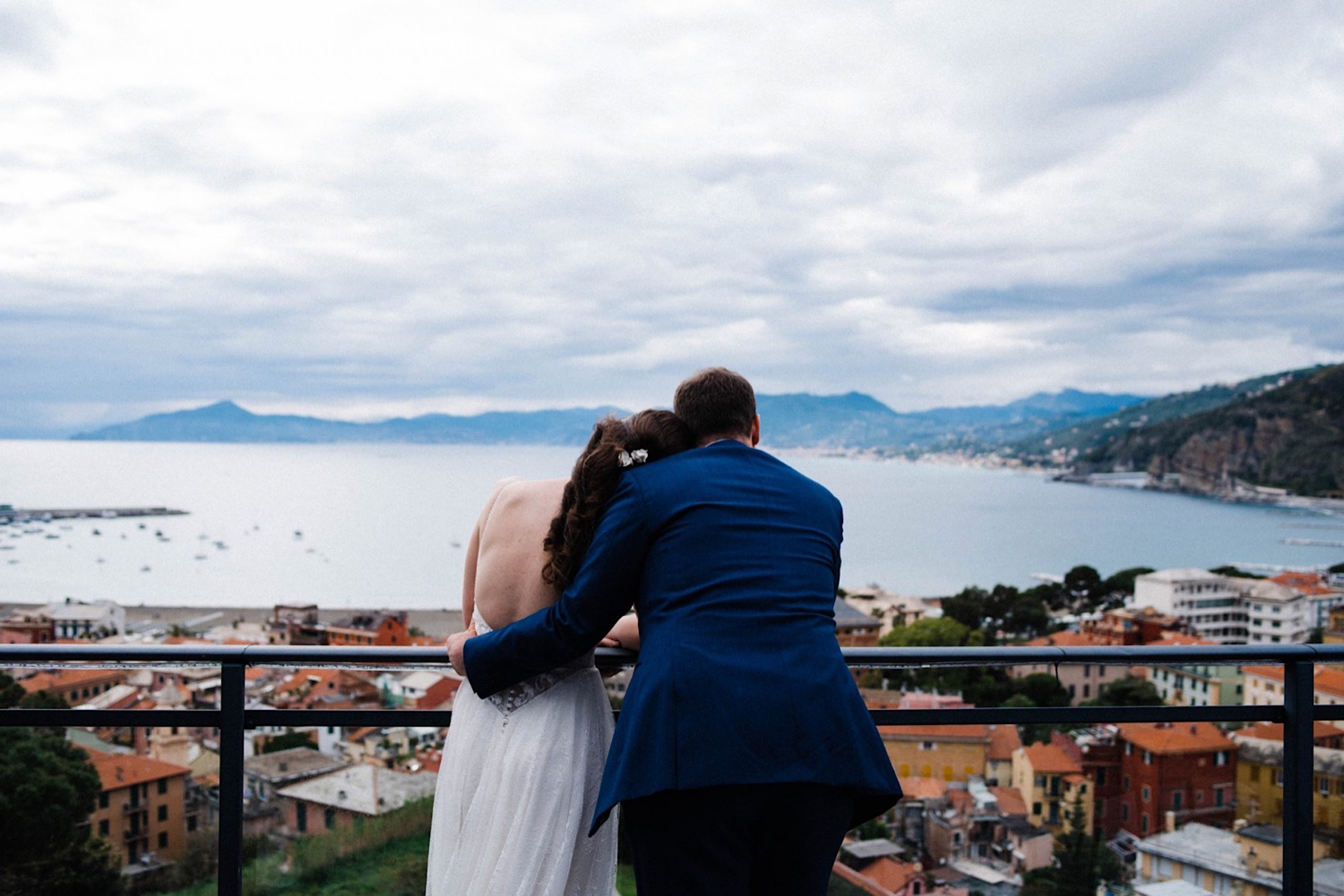 A relaxed wedding portrait of the bride & groom looking out over the Bay of Fables in Sestri Levante, from the Hotel Vis À Vis Rooftop.