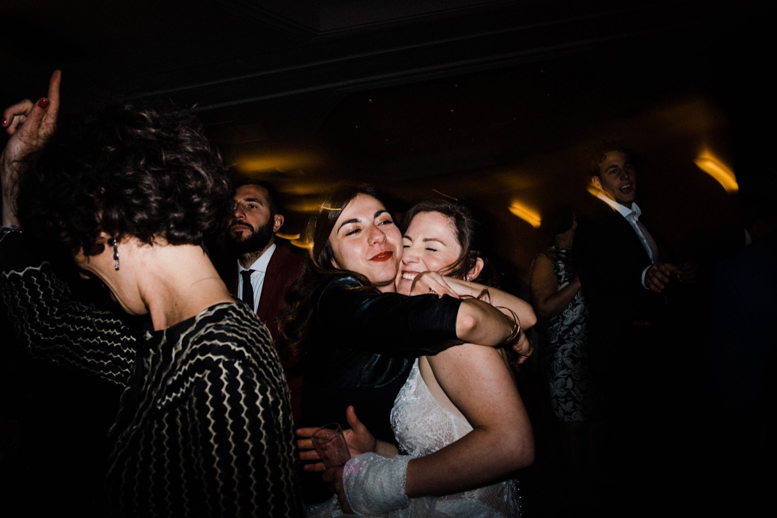Candid Wedding Photography of a guest hugging the bride on the dance floor.