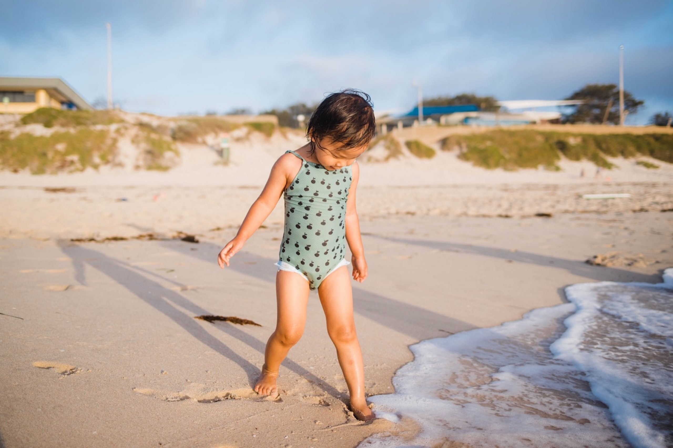A little girl sticks her feet just into the edge of the ocean, with the sand dunes behind her.
