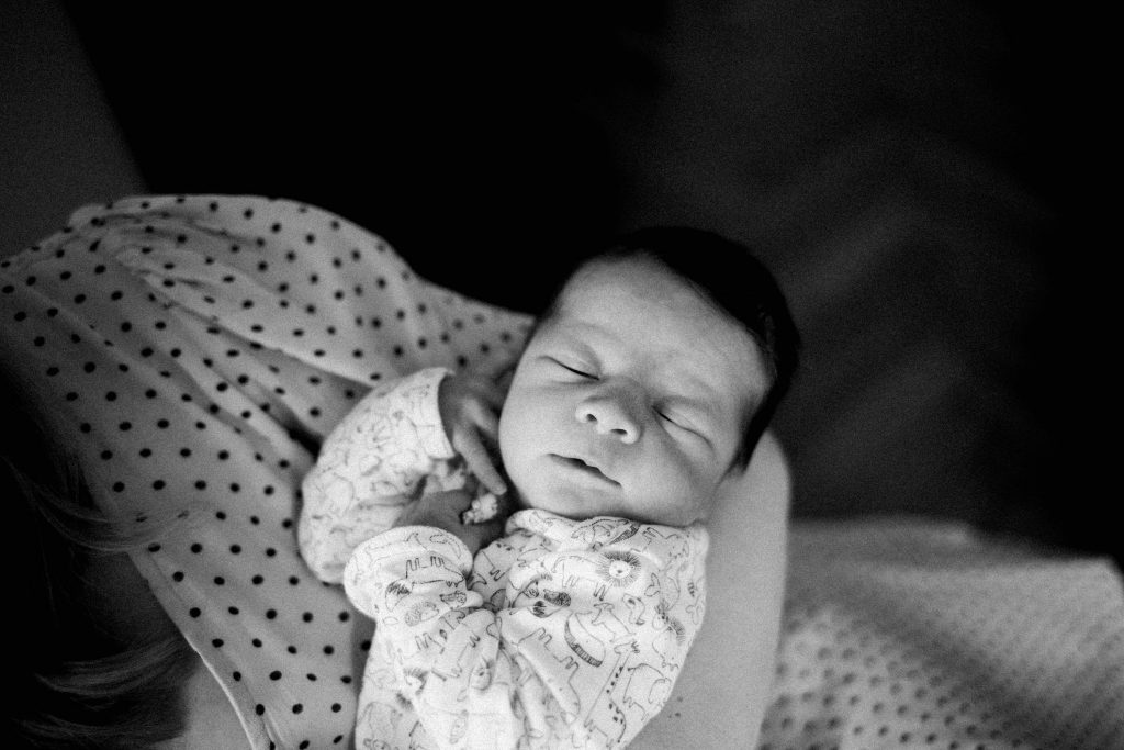 Black and White photo of a newborn baby in his Mum's arms, taken at home in Milan, Italy.