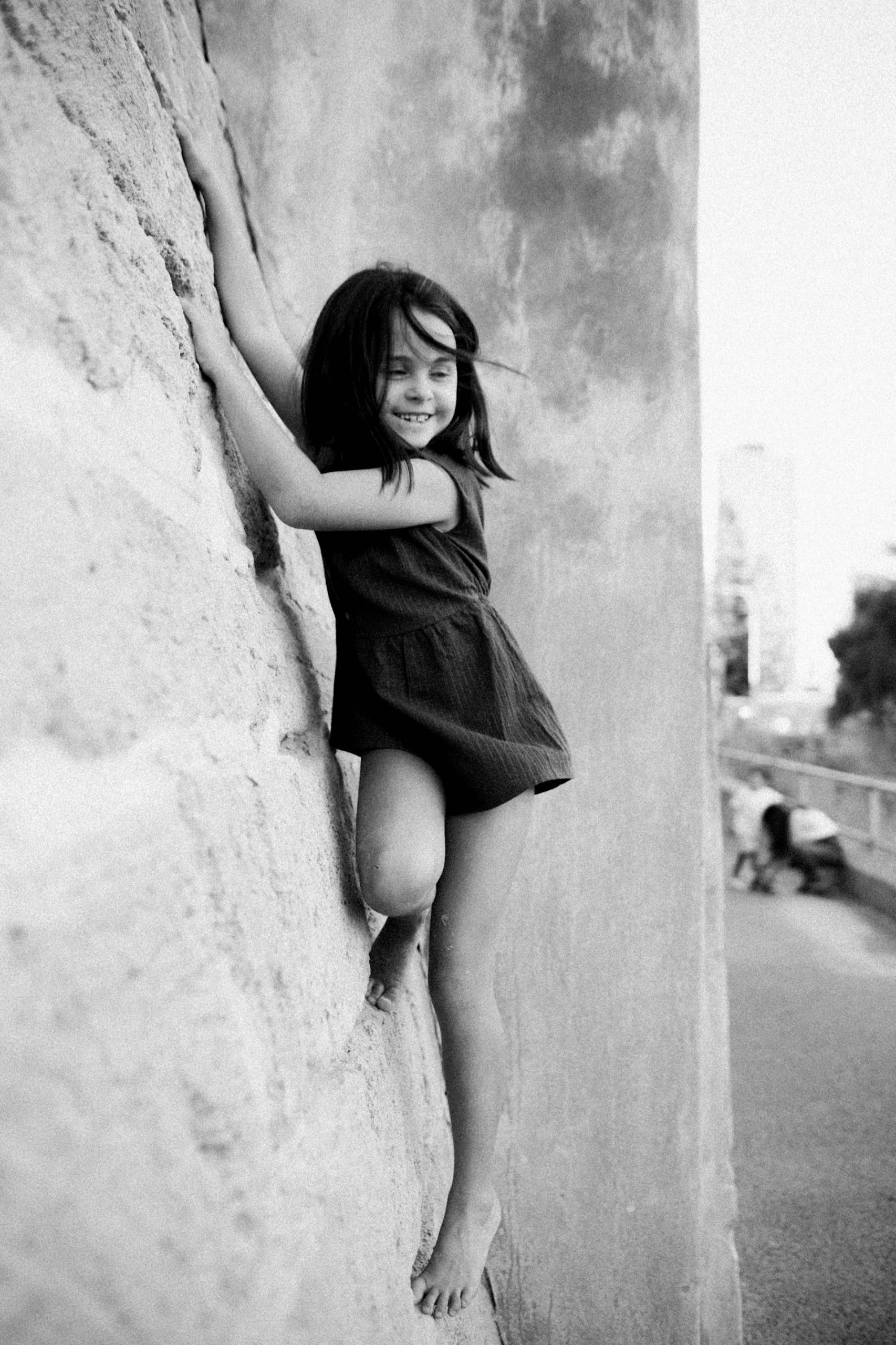 A black and white natural family photo of a girl climbing up an angled limestone wall.