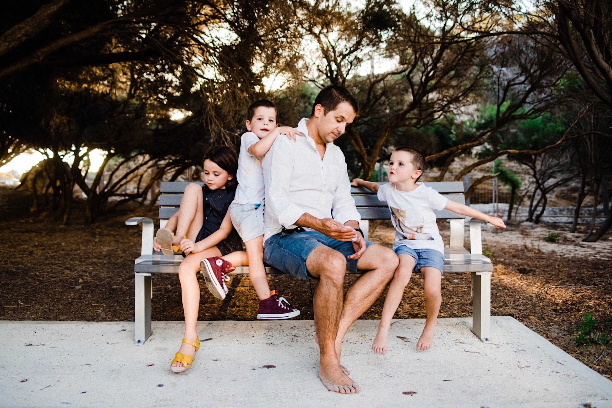 Candid Fremantle Family Photography of a Dad sitting on a park bench, surrounded by his three children - one hanging off of his shoulder, on sitting putting her shoes on, and one sitting talking to him.