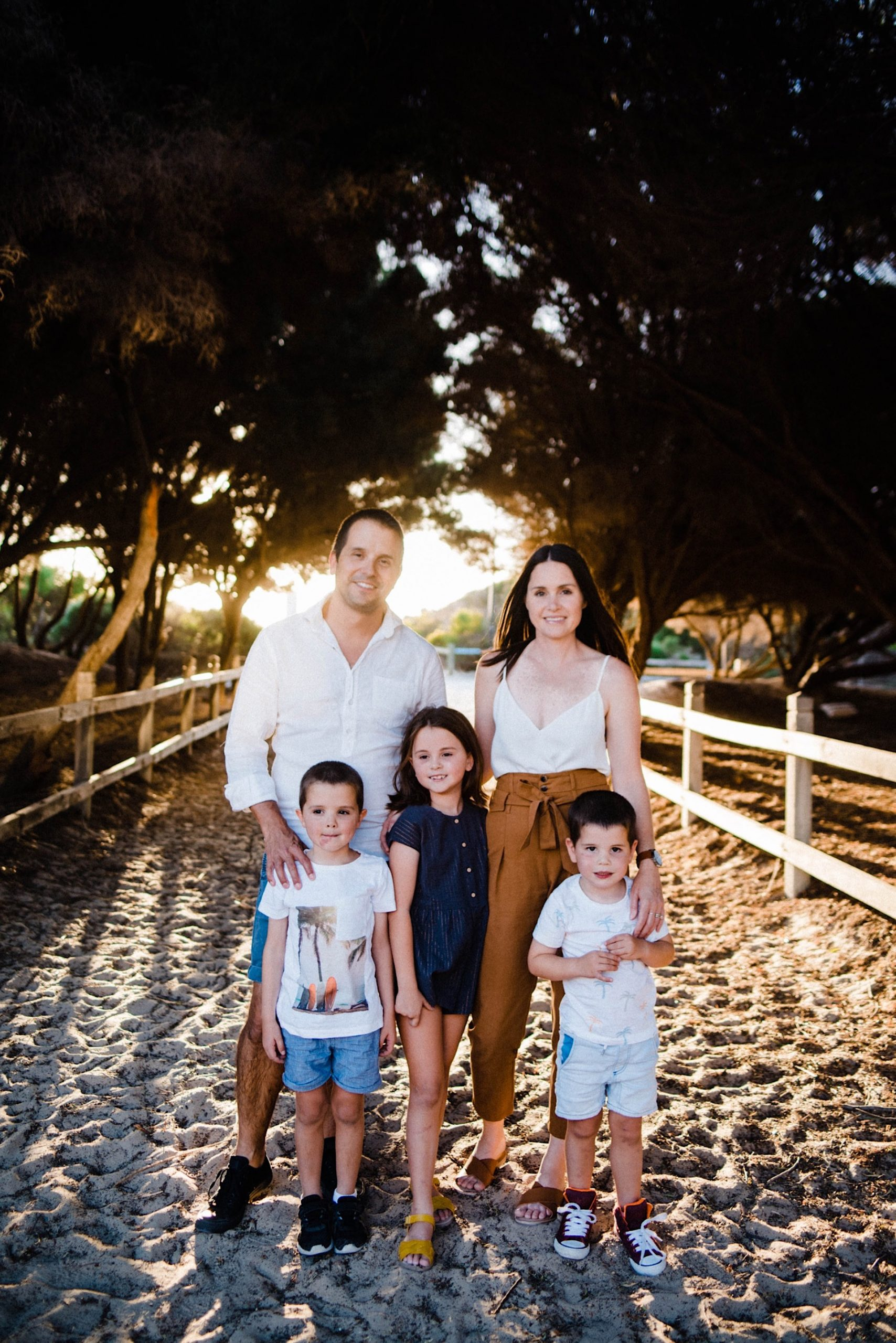 A portrait-oriented photo of a family of five standing on the beach, surrounded by trees, with golden light in the background.
