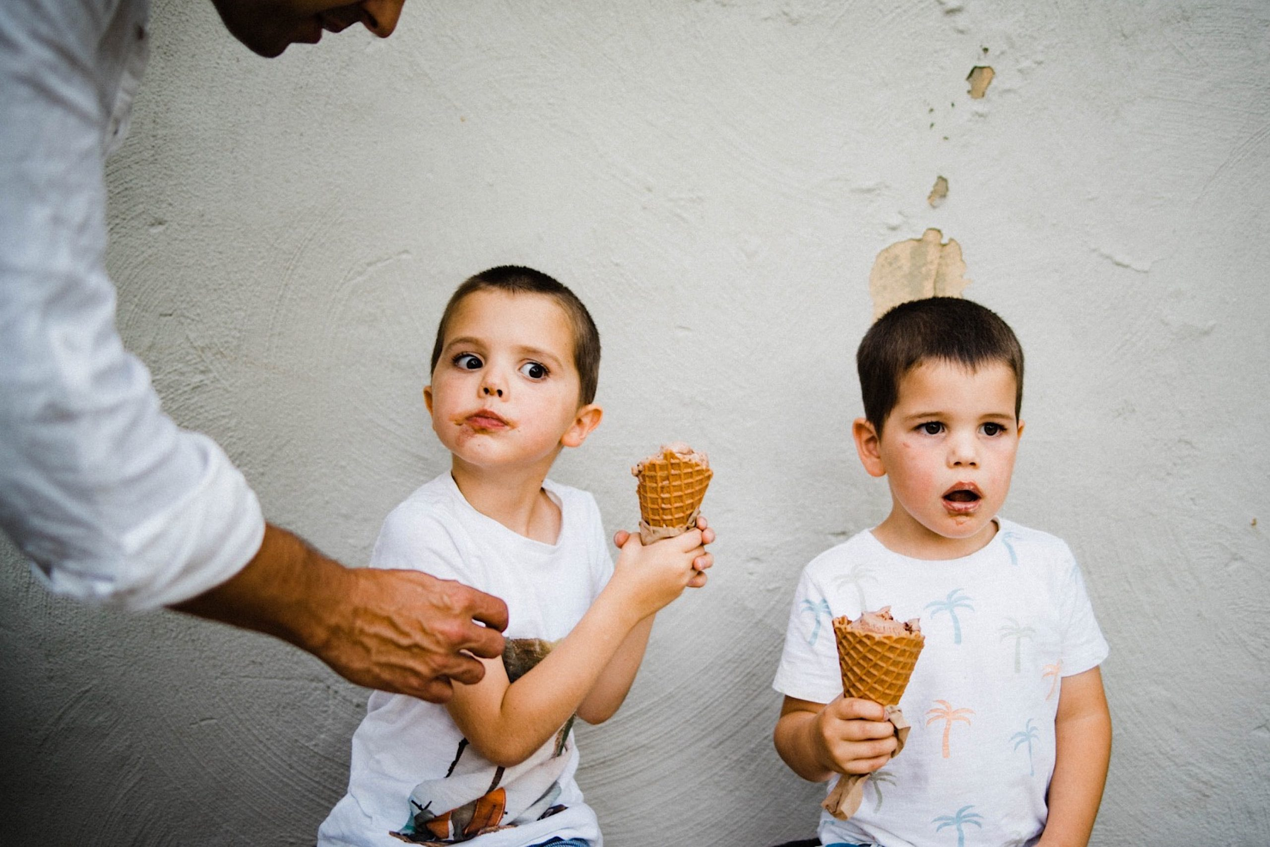 A candid Fremantle family photo of two brothers eating ice cream from Kuld Creamery in Fremantle, one looking upset and pulling his ice cream away from his Dad, who's reaching over to try his ice cream.