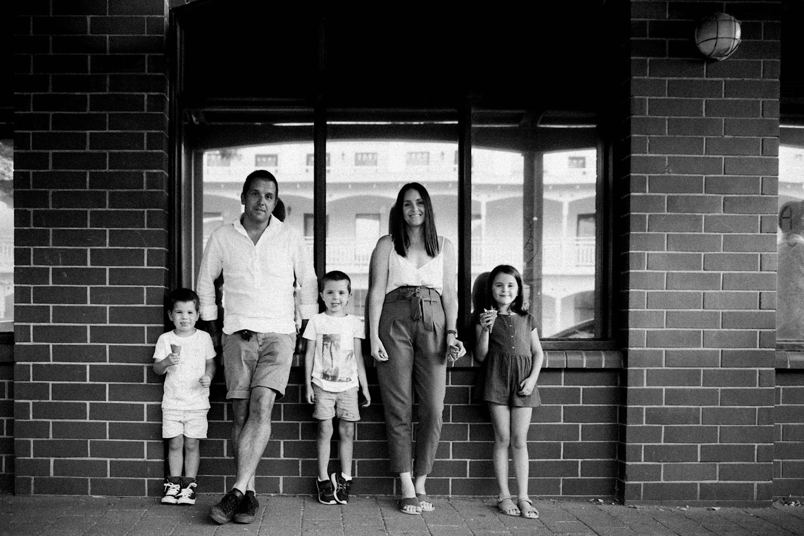 Black and white family portrait of a family of five standing, leaning against a building.