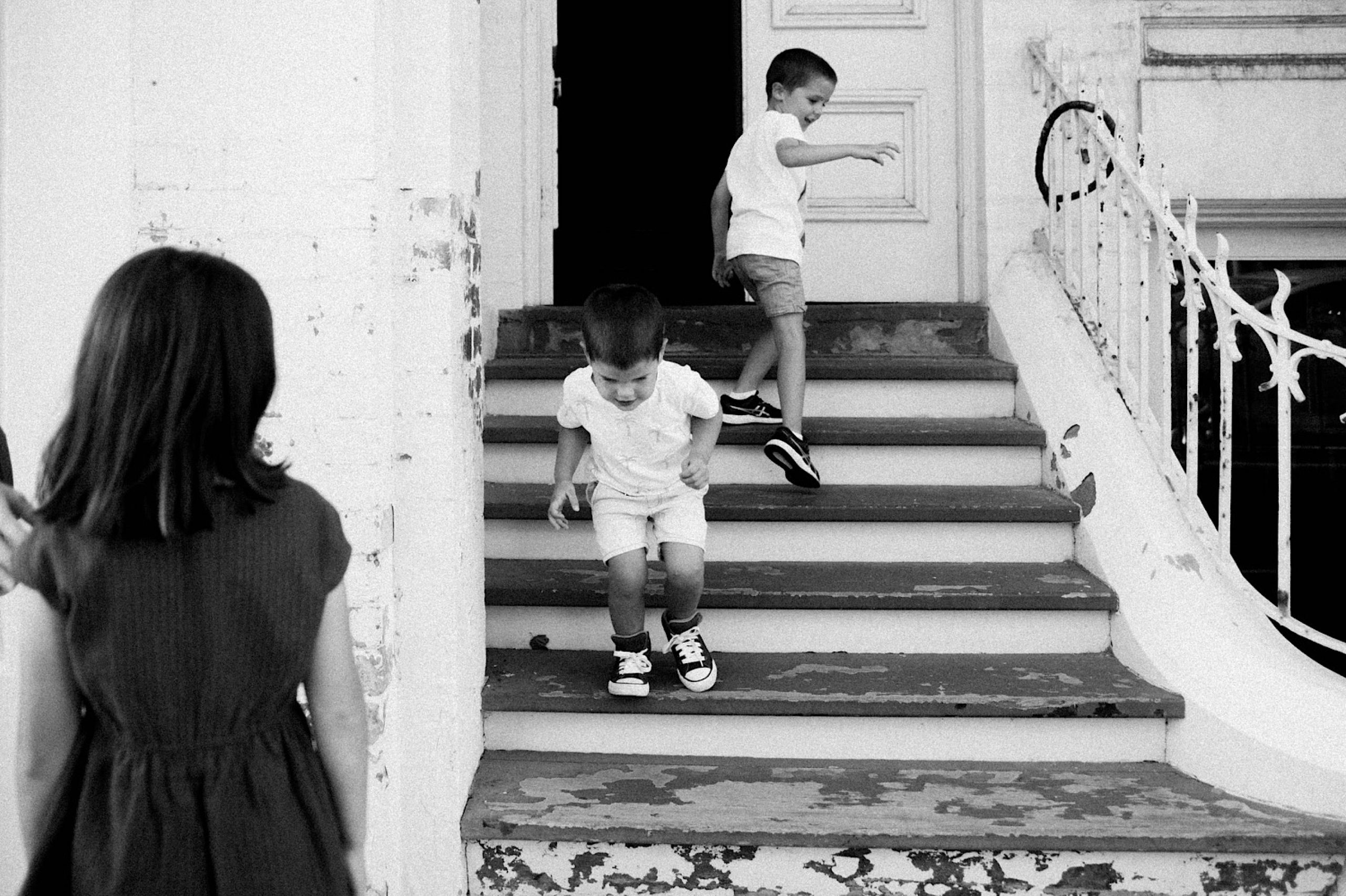 A black and white wide family photo or two boys playing on stairs. Their sister stands on the left side of the photo watching on.