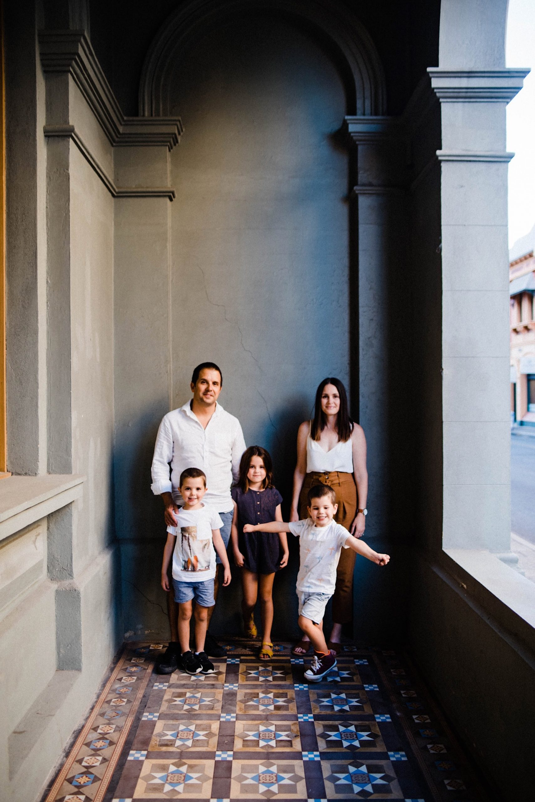A portrait-oriented family portrait - the family of 5 are standing in a portico with dark grey-blue walls and patterned tiled floors.