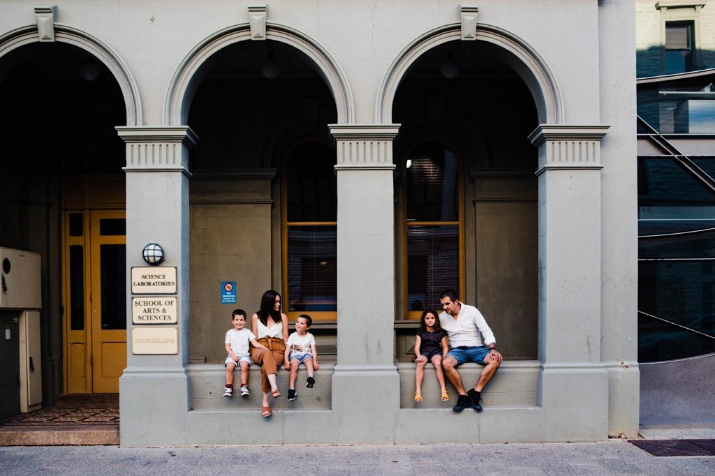 A portrait of a family of five, sitting in the archways of an old building in Fremantle, the two boys sitting with their Mum on the left side, and the girl sits with her Dad on the right.
