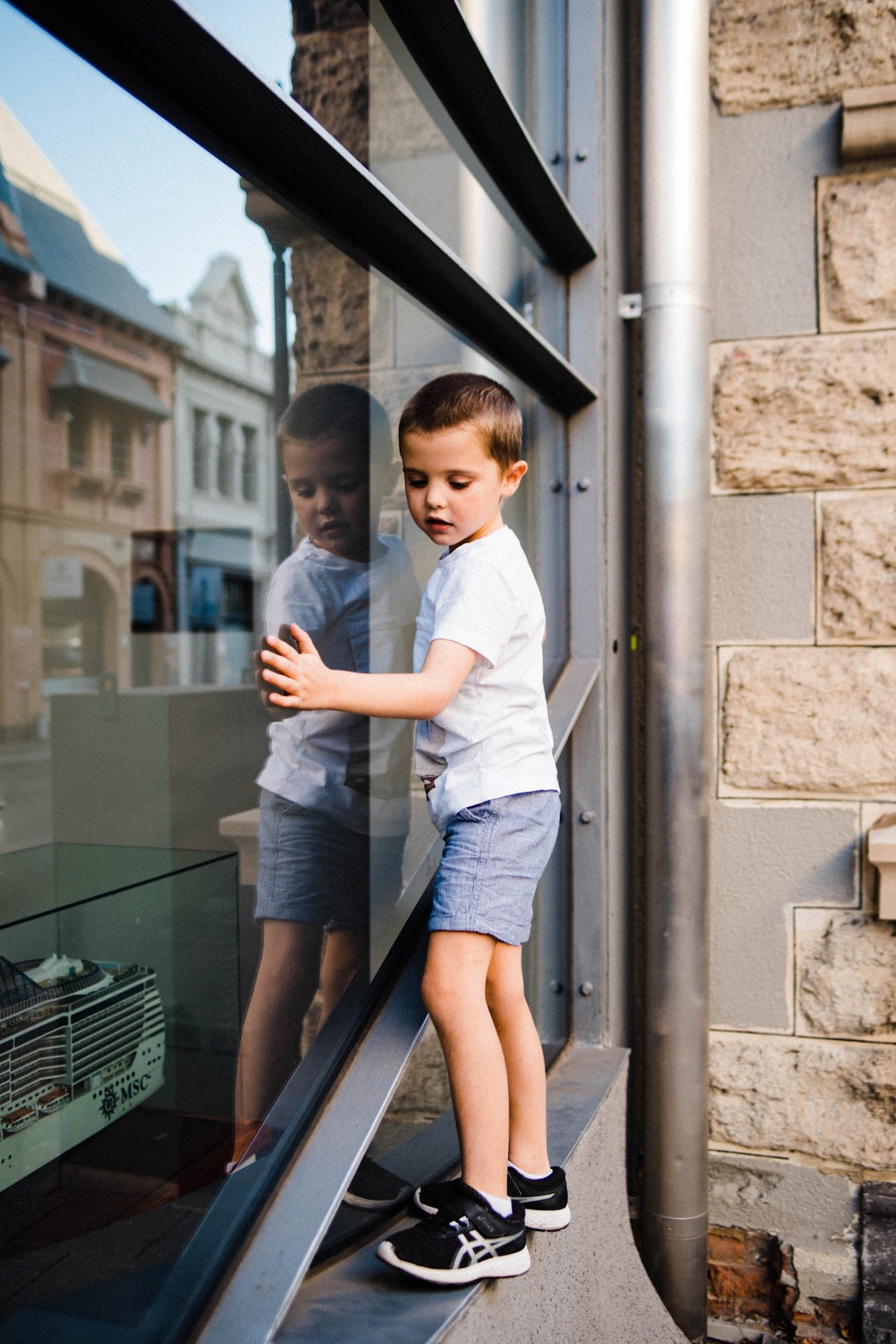 Candid Fremantle Family Photography of a child climbing the metal beams that line a big glass window. His reflection is mirrored in the window.