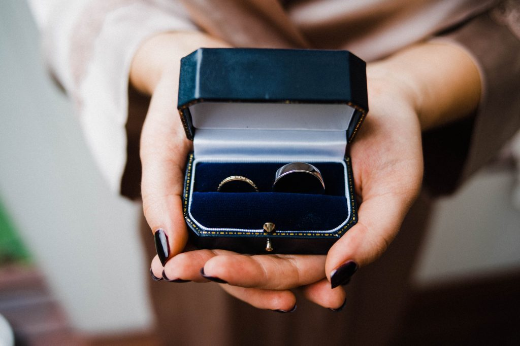 A bride holds her wedding rings, made sustainably by Digby and Iona, in her hand in a blue jewellery box.