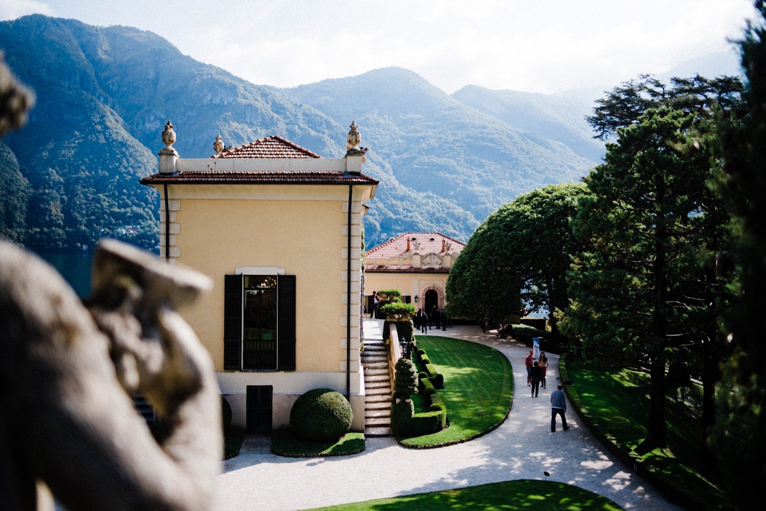 A wide photo showcasing Villa del Balbianello, in Lenno, on Lake Como. On the lower left corner, the details of a statue a blurred out, in the rest of the photo you see the Villa, the surrounding gardens and the mountains in the background.