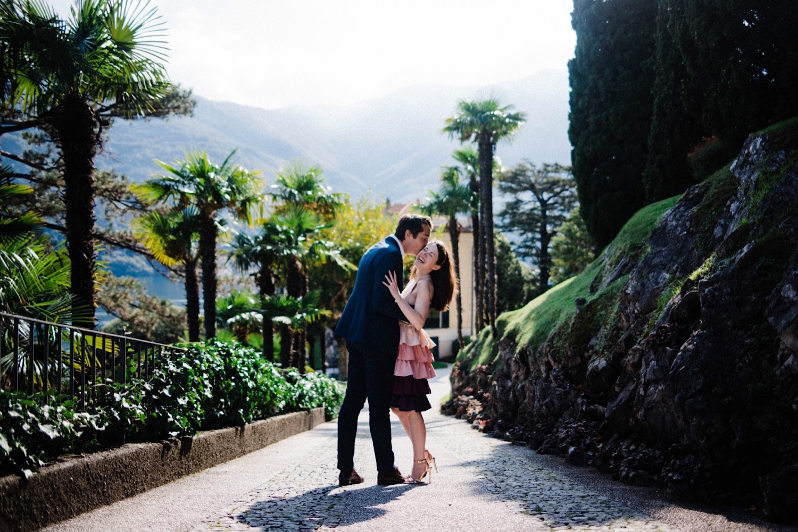A wide photo of a couple standing in the middle of a laneway at Villa Balbianello on Lake Como, surrounded by palm trees.
