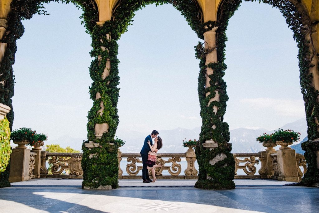 Villa Balbianello Portrait Photography featuring a wide shot of a couple standing against the main verandah, shot through the Villa's famous arches surrounded by vines.