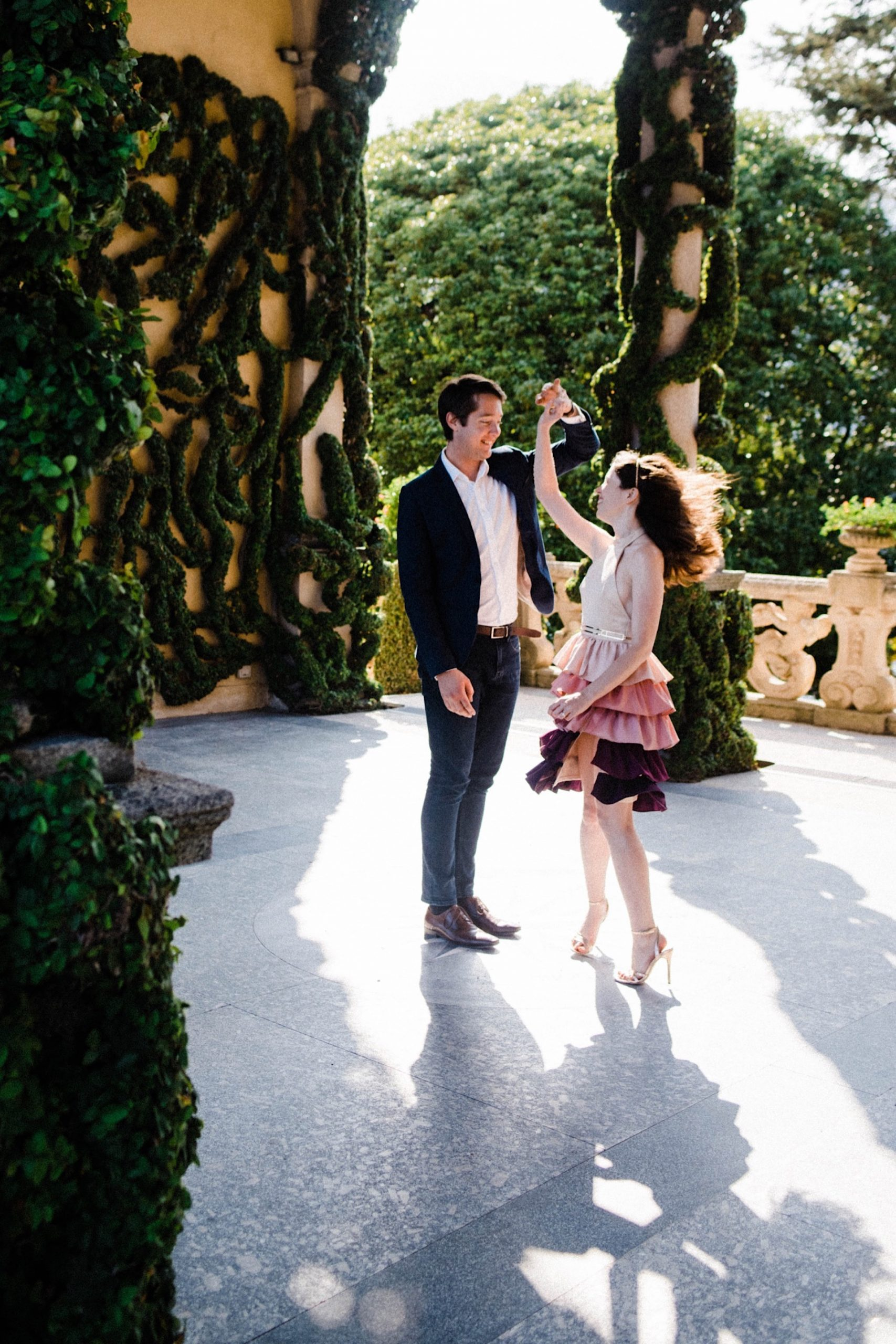 A romantic portrait photo of a couple dancing together in the centre of the main courtyard at Villa Balbianello in Lenno, on Lake Como.