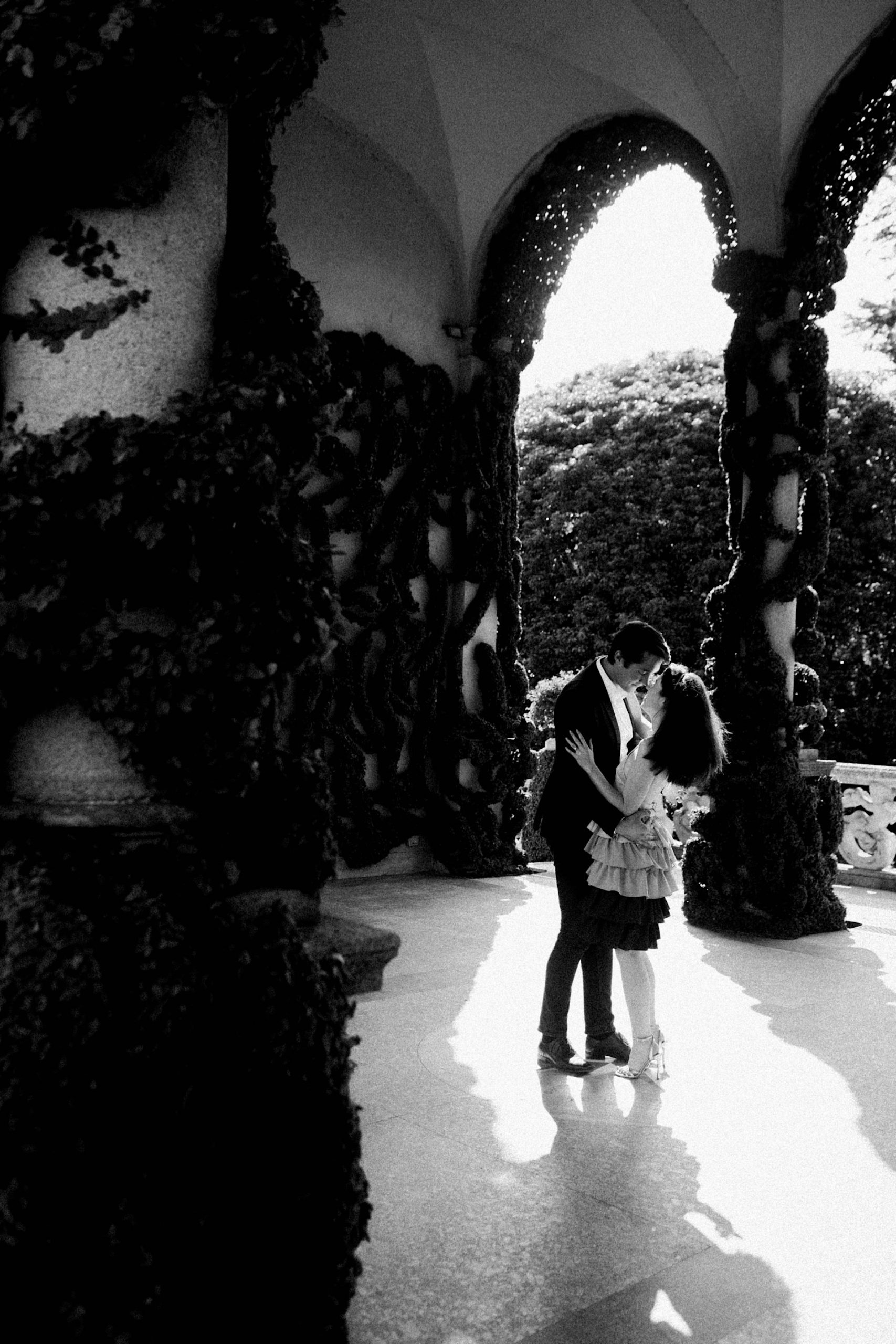A black & white wide portrait photo of a couple standing in a patch of sunlight sharing a kiss.