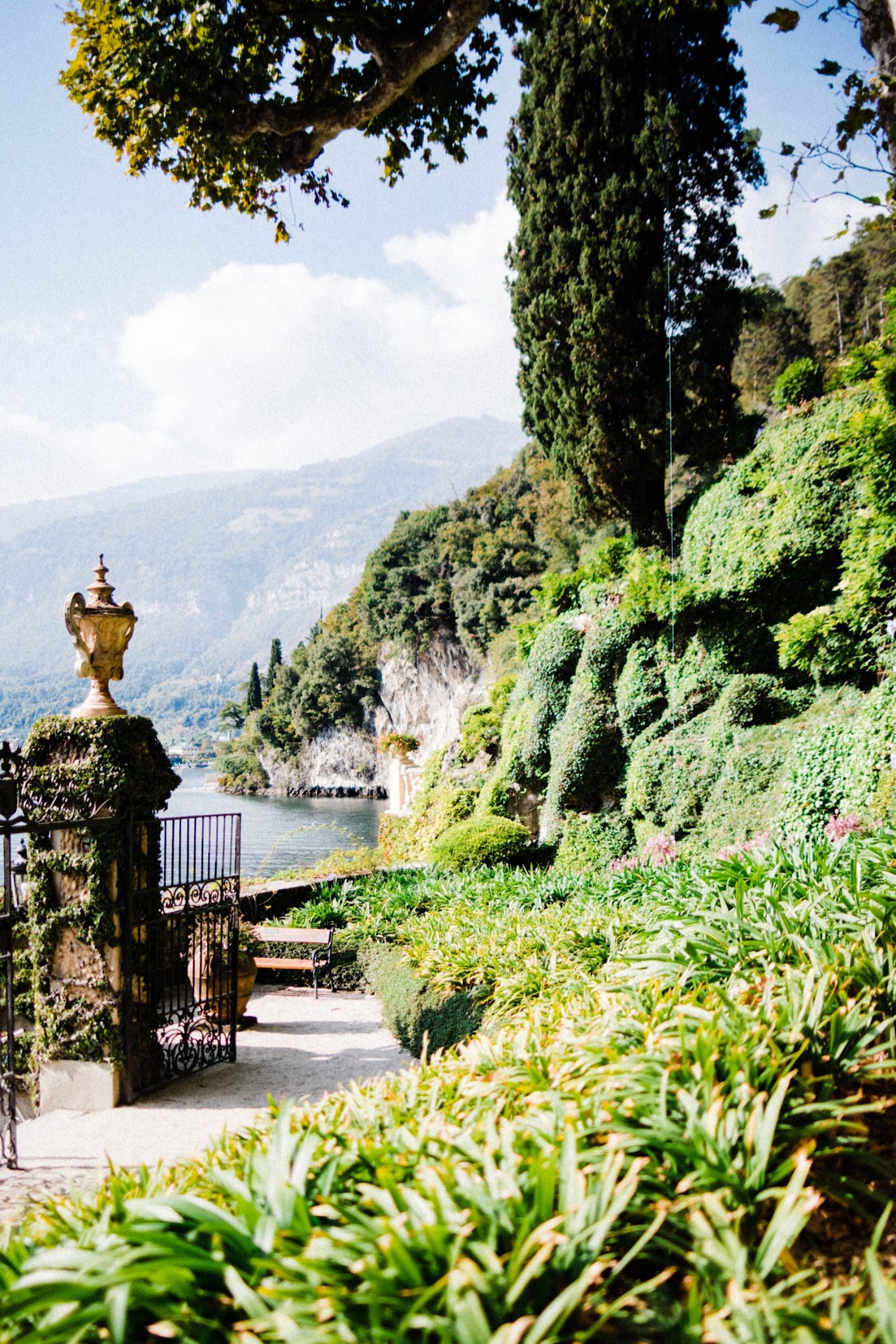 A portrait image of the gardens at Villa Balbianello, looking out over the gardens just in front of the main gates, and a view out over Lake Como.