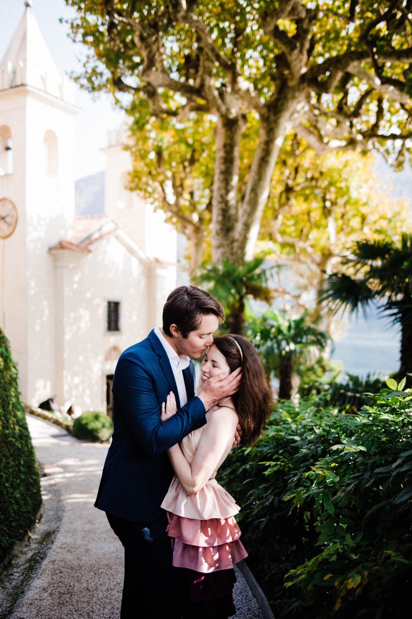 A portrait photograph of a couple standing together, sharing a kiss, in the gardens at Villa Balbianello.
