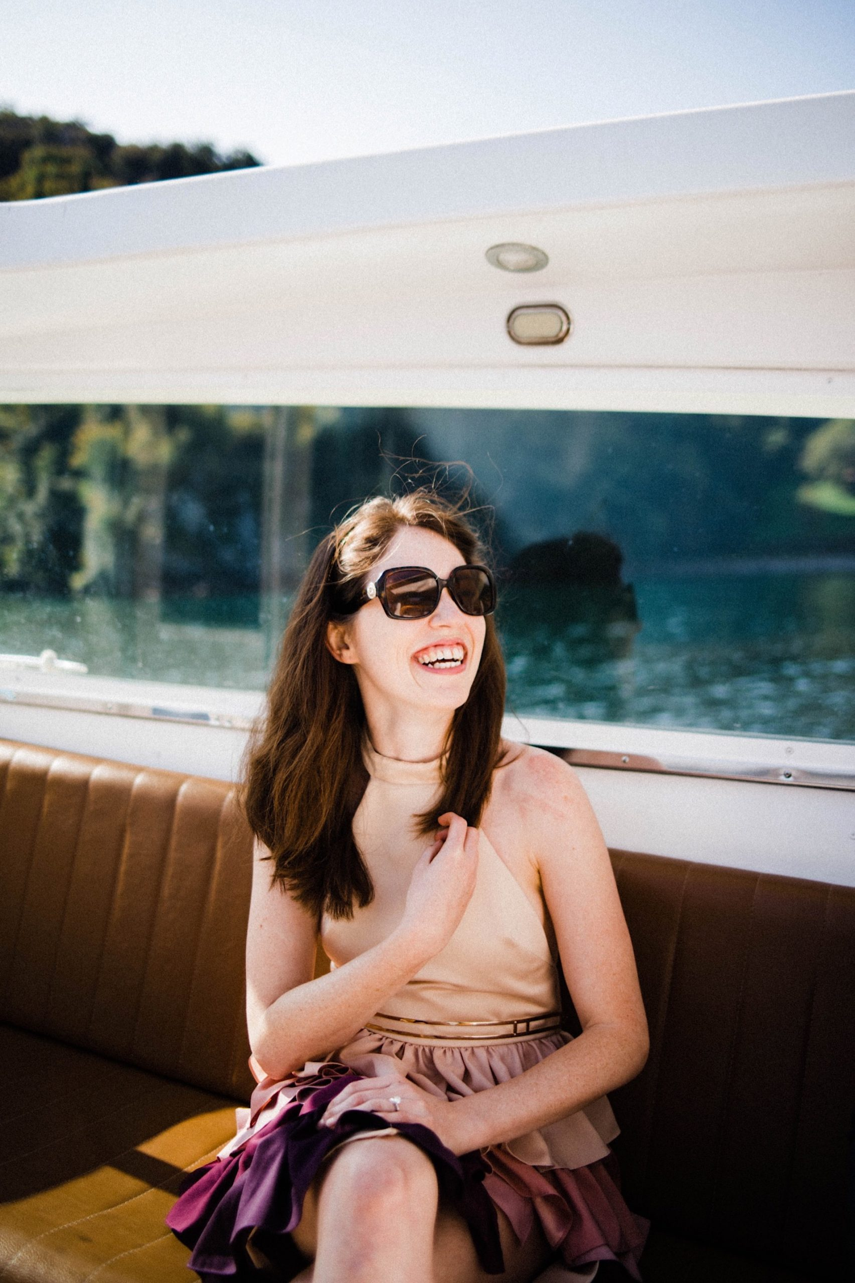 A portrait photo of a woman sitting and laughing in the back of a small boat, that's travelling from il Lido di Lenno to Villa Balbianello on Lake Como.