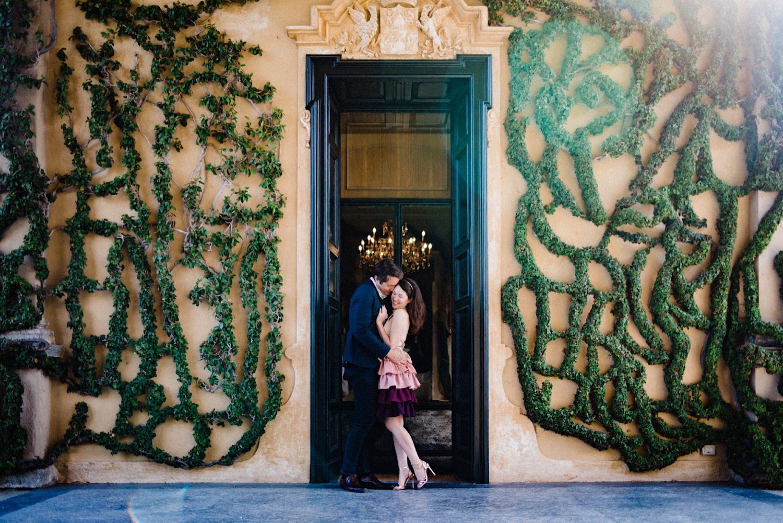 A wide shot of a couple standing in a doorway, the walls around it are covered by intricately patterned climbing hedges.