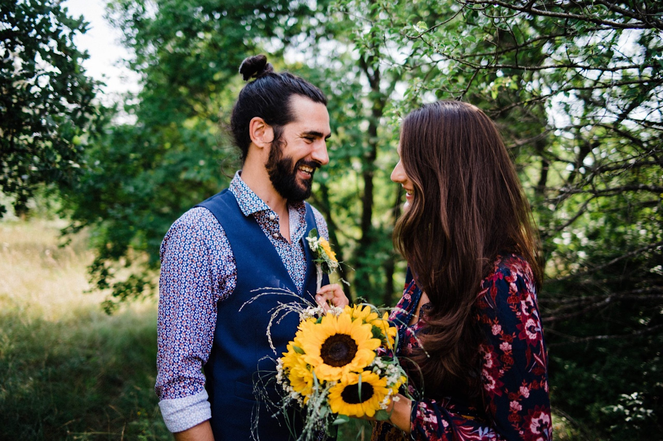 Photo of a newlywed couple smiling at each other in the Slovenian woods - the bride holds a bouquet of sunflowers..