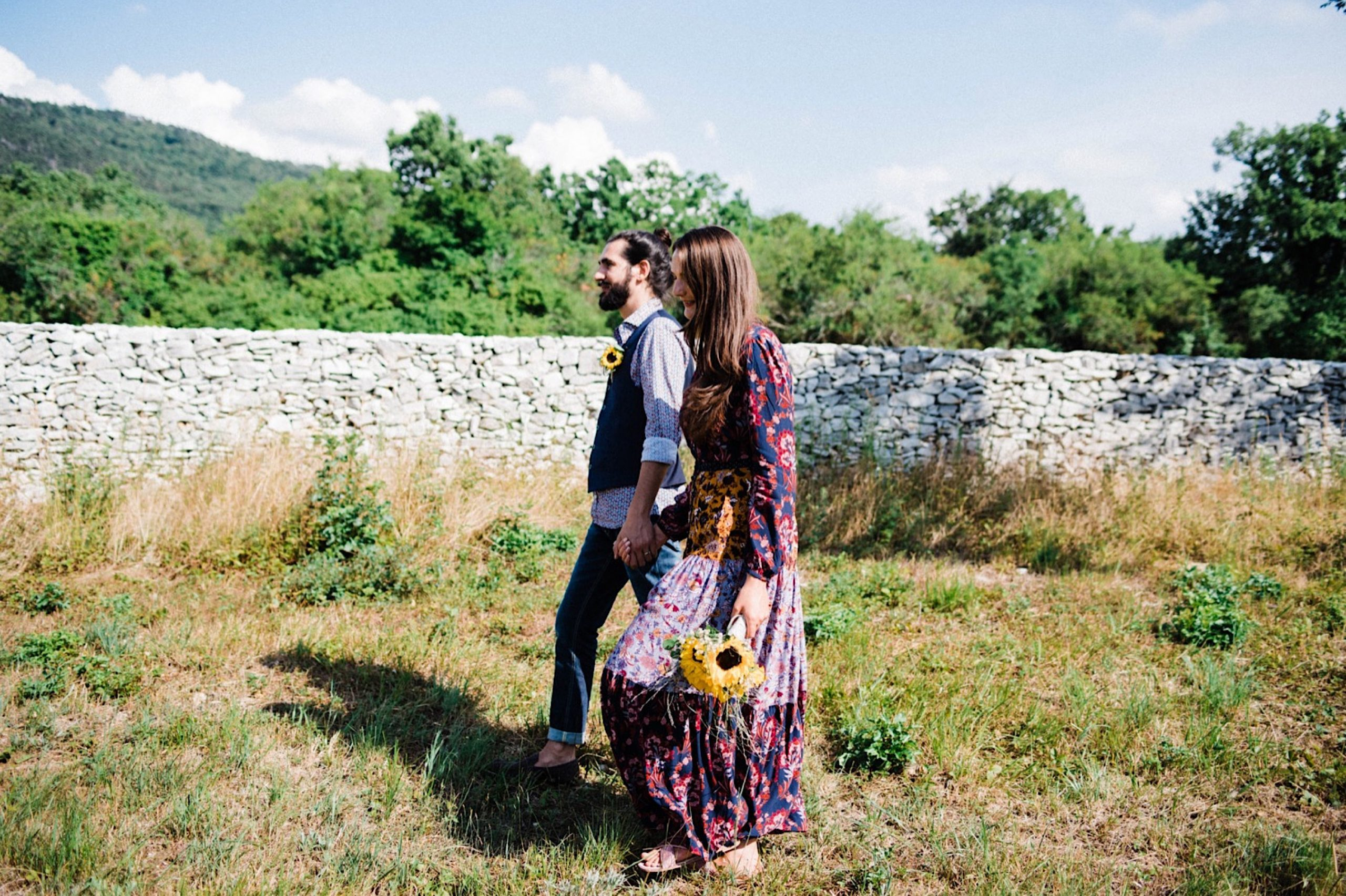 A newlywed couple, wearing brightly patterned wedding clothes, walk through a field in the Slovenian countryside.