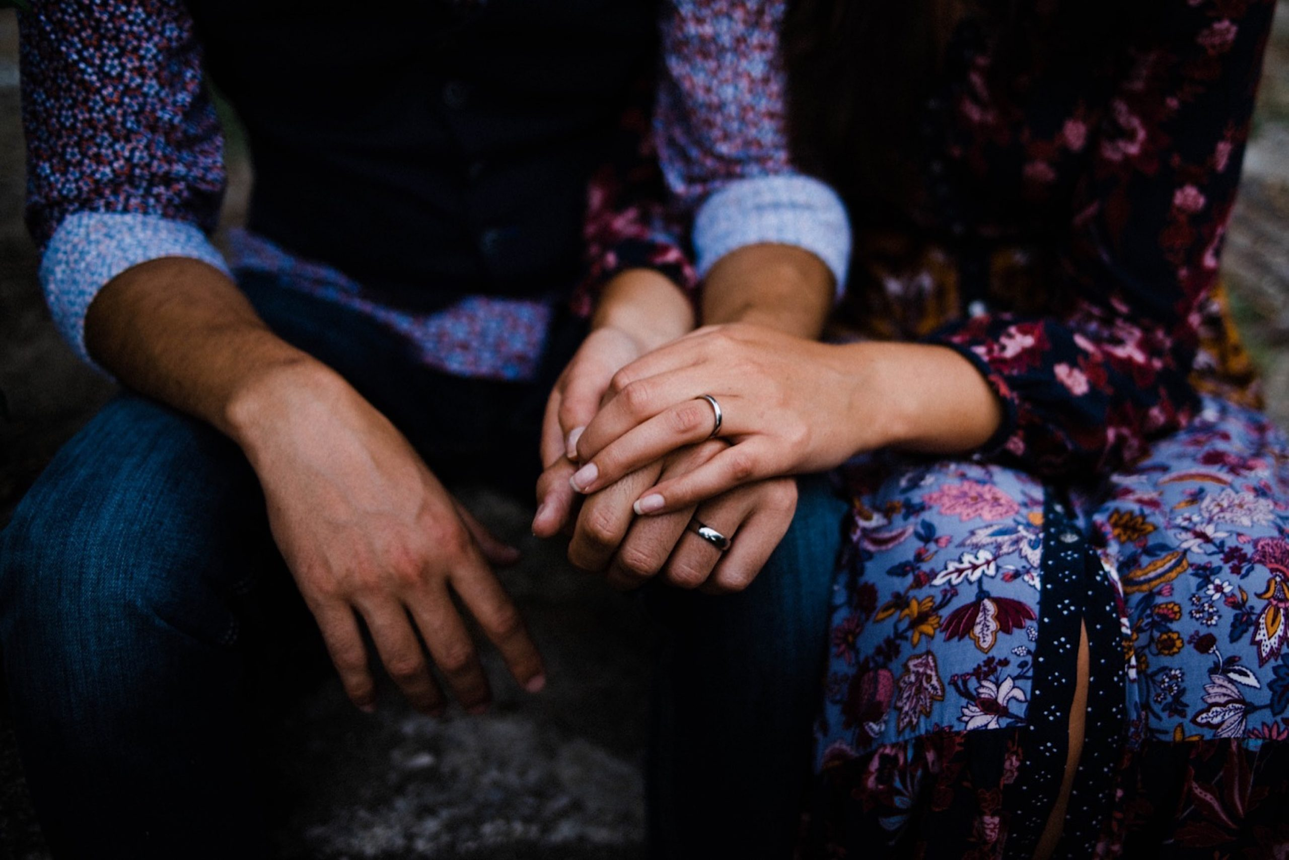 Italian Wedding Photography of a couple sitting down and holding hands. They both wear colourful wedding clothes and the photo showcases their wedding rings.