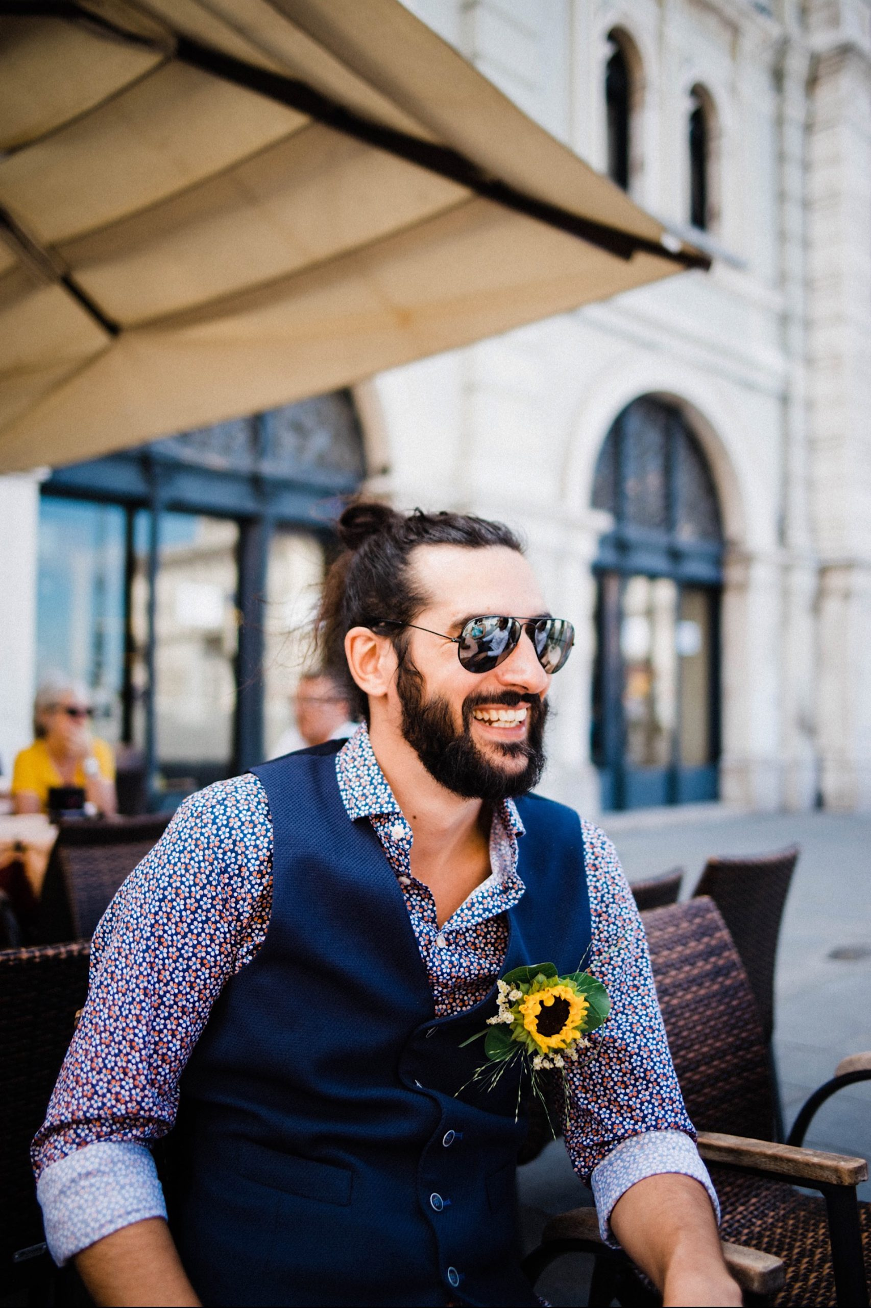 Portrait-oriented mid-shot of a groom smiling, sitting at a cafe in Piazza Unità in Trieste.