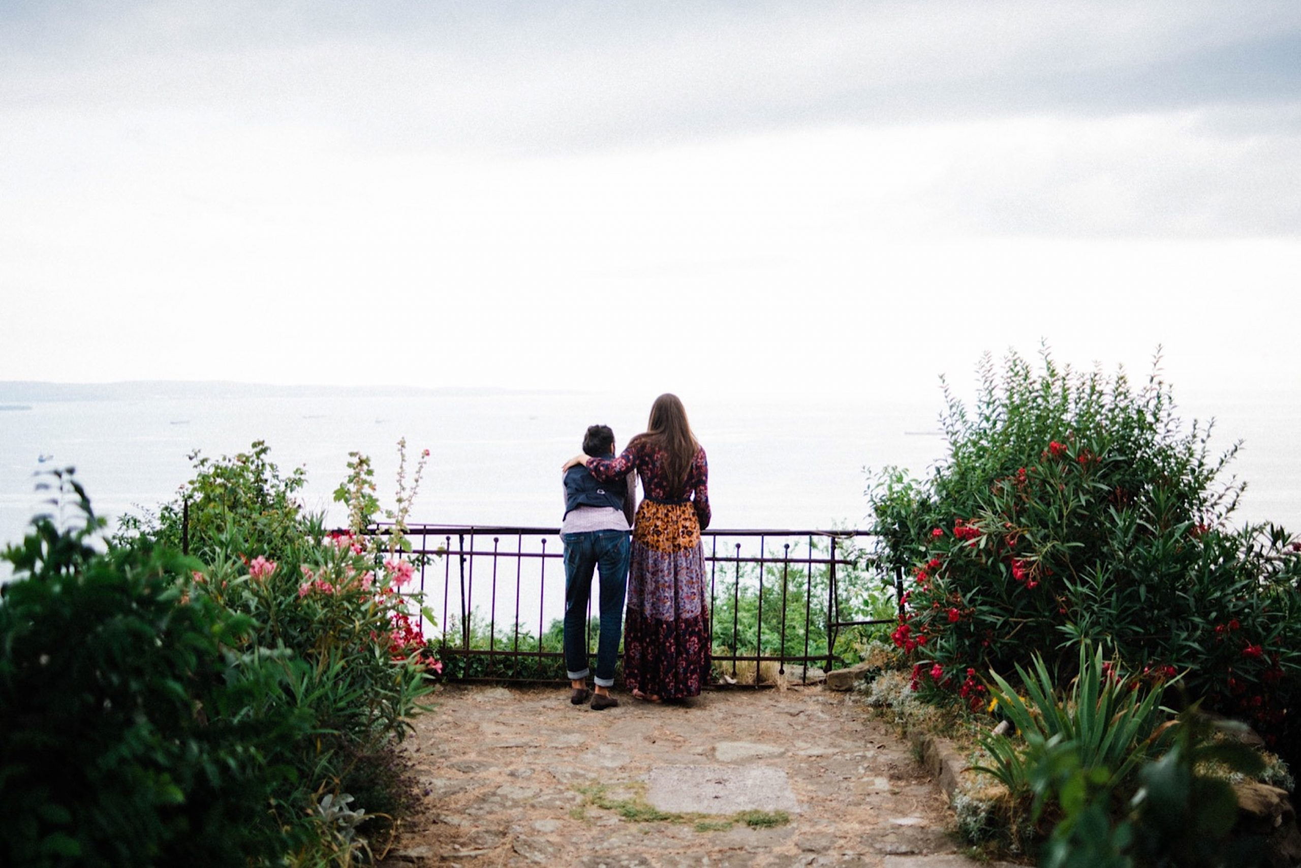 A wide photo of a newlywed couple leaning on a fence, surrounded by a summer garden and looking out over Trieste's Adriatic Sea.