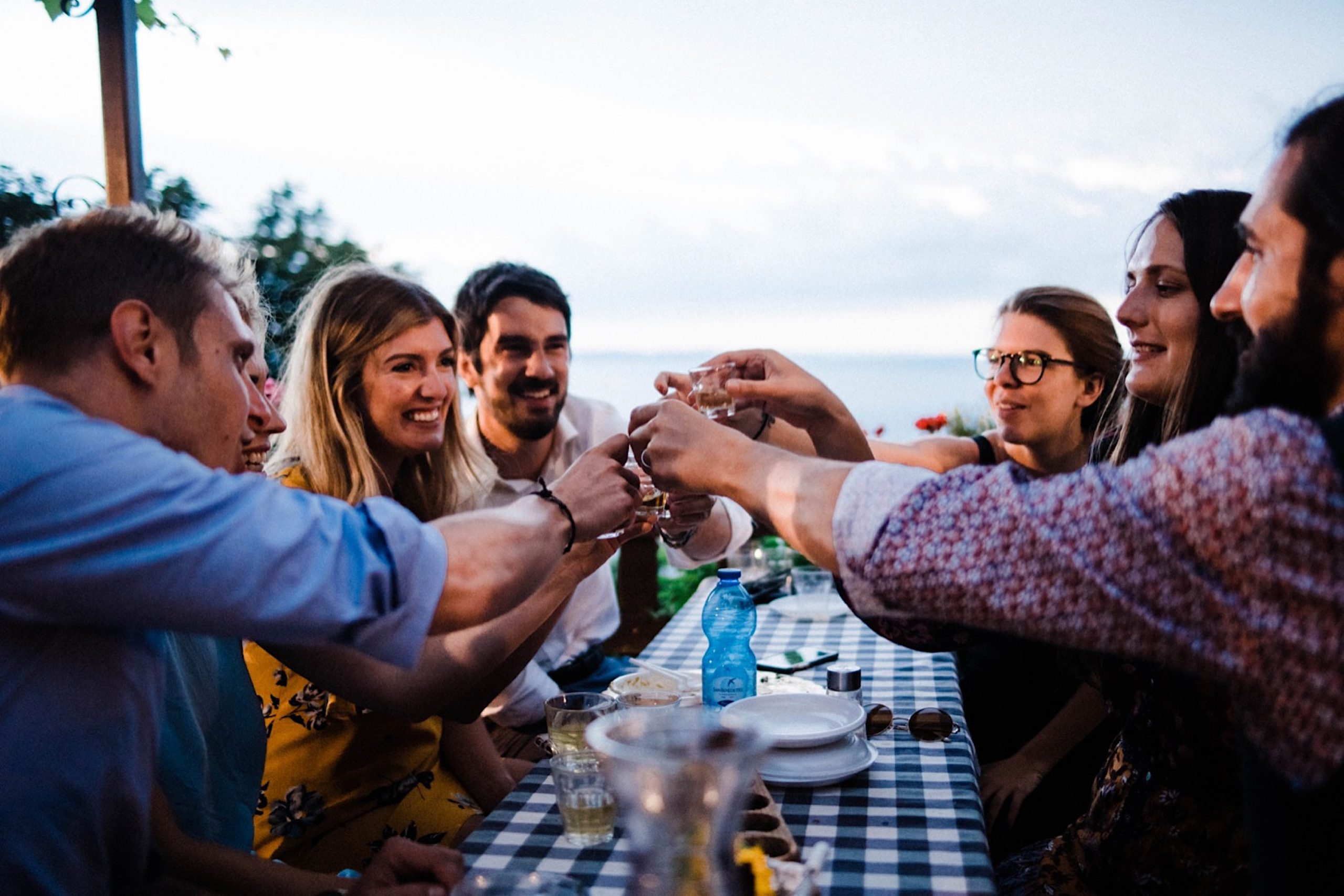 A group of destination wedding guests cheer with grappa shots, at an Osmiza in Trieste, looking out over the Adriatic Sea.