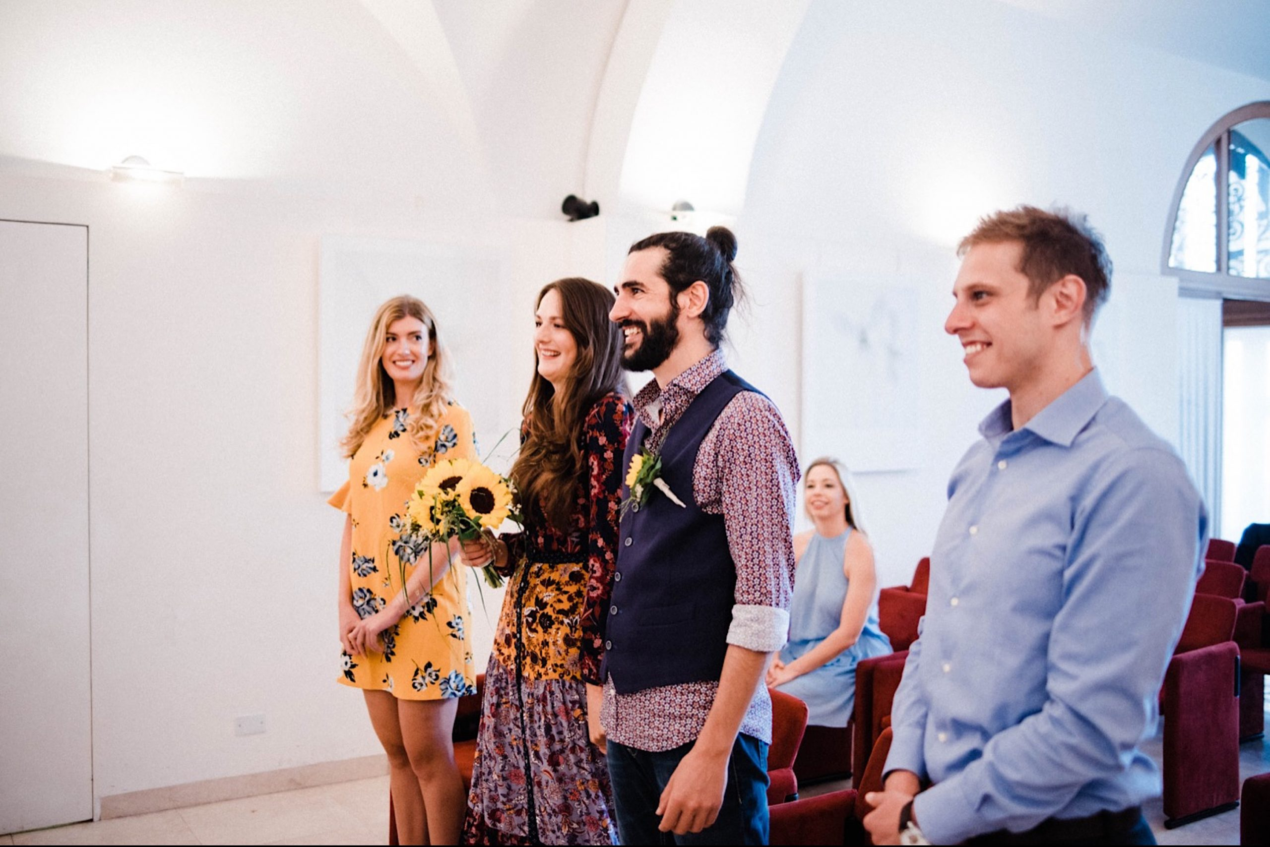 Wide photo of a bride, a groom and their witnesses in the Sala Bobi Bazlen, Trieste.