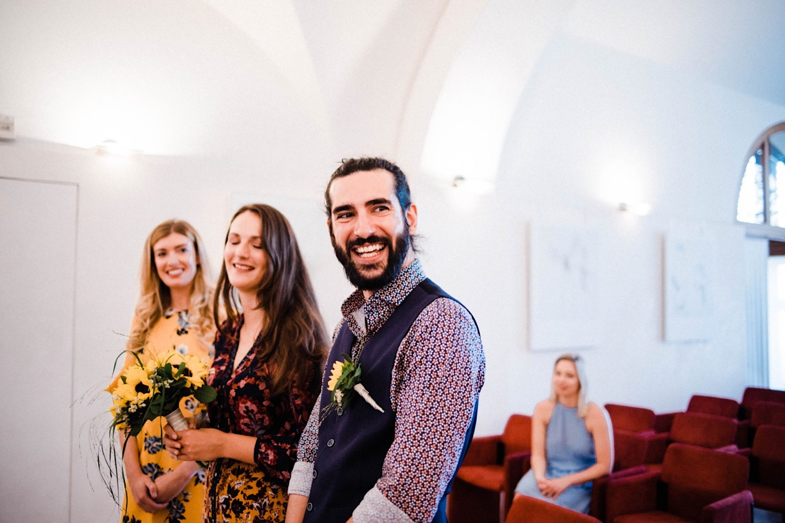 A wide photo of newlyweds smiling in the Sala Bobi Bazen in Trieste, Italy.