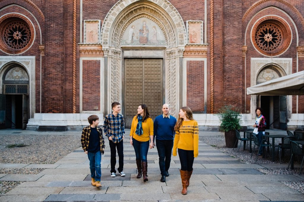 A wide photo of a family walking in front of one of Milan's Chiesa del Carmine.