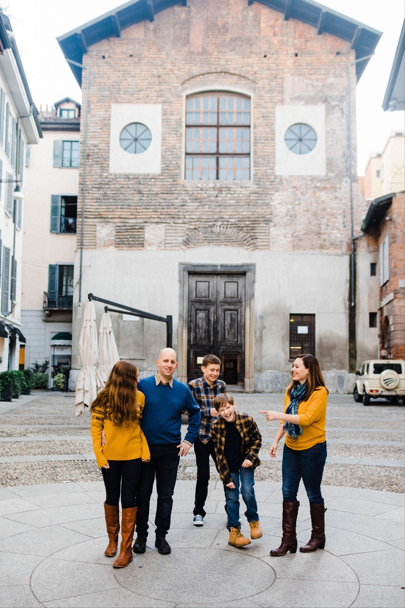 Portrait photo of a family all laughing, standing in a piazza in Milan.