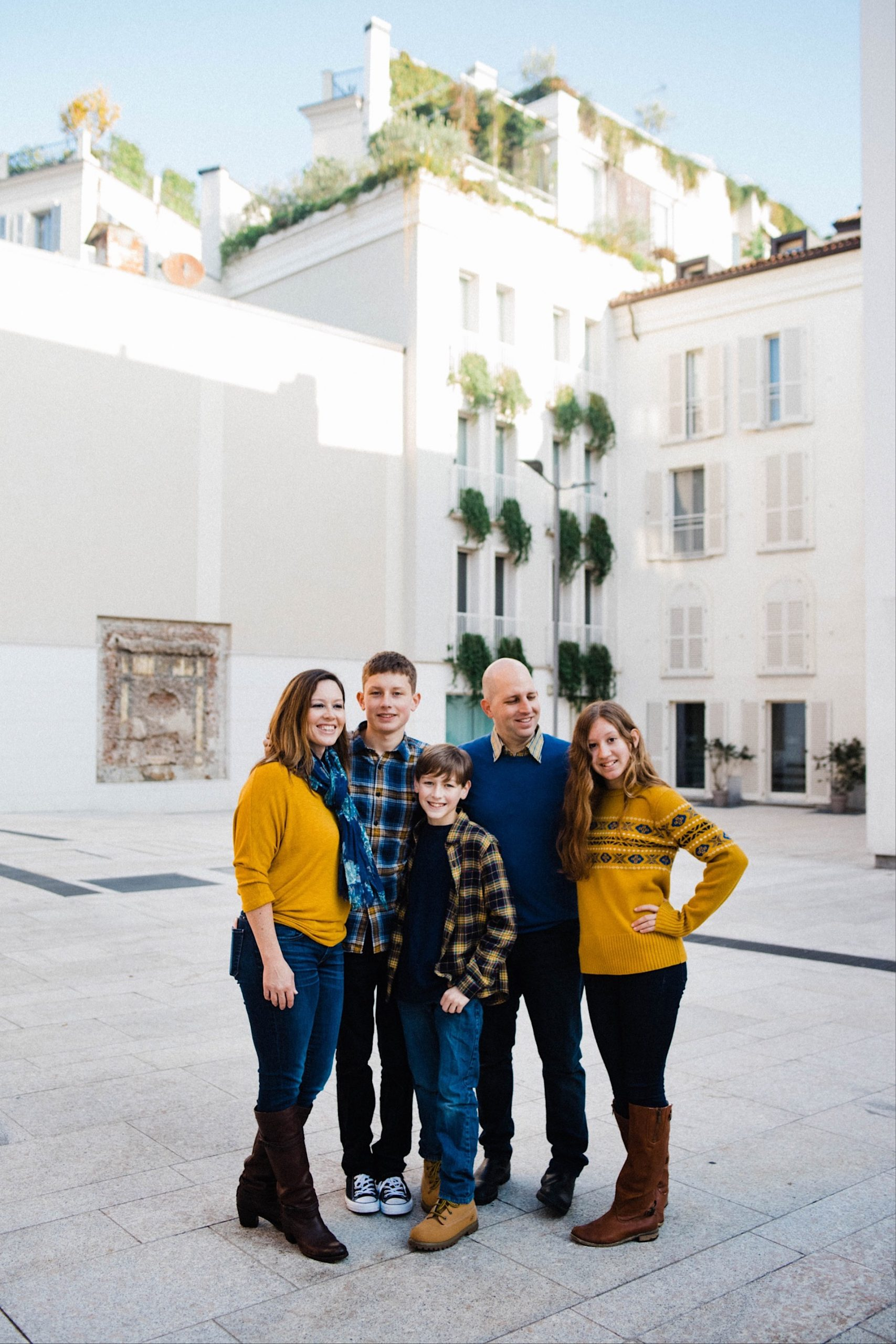 Family Photography in Milan, taken at Piazza Borromeo, of a family with three teenagers standing together and smiling.