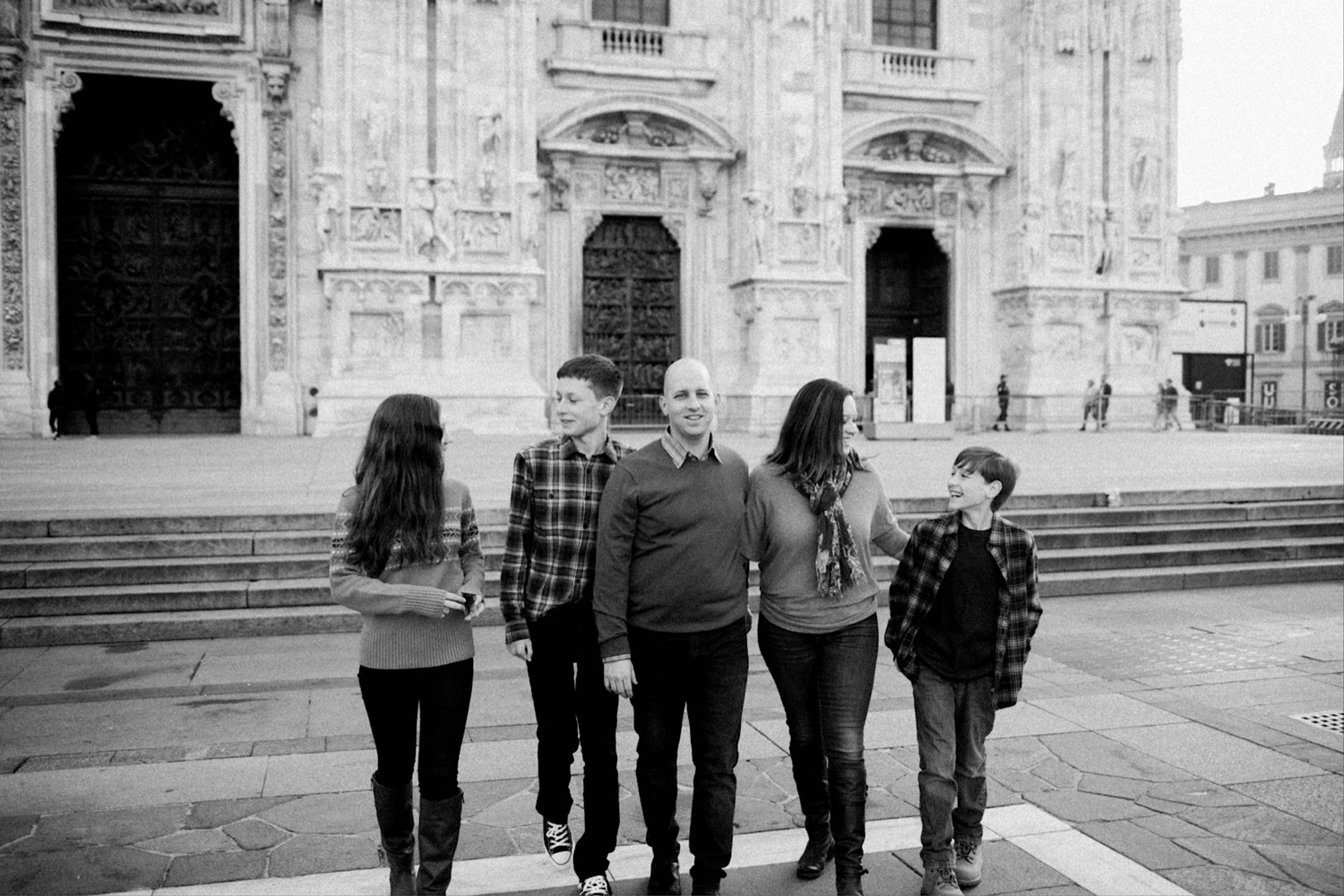 Black & white family photo of a family of five walking in front of the Duomo di Milano.