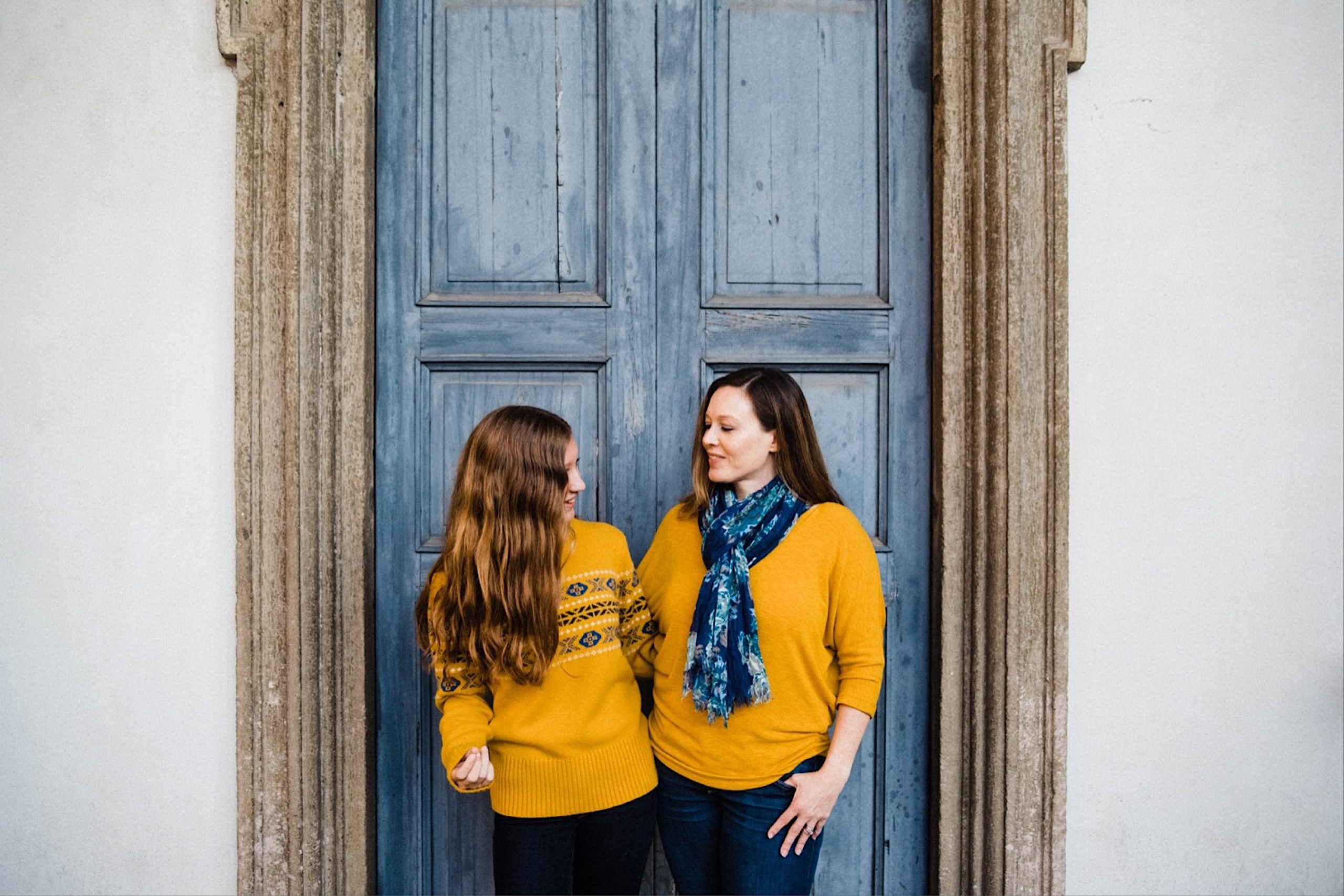 Portrait photo of a mother and daughter standing together, smiling. They both wear yellow sweaters and are standing in front of a blue door.