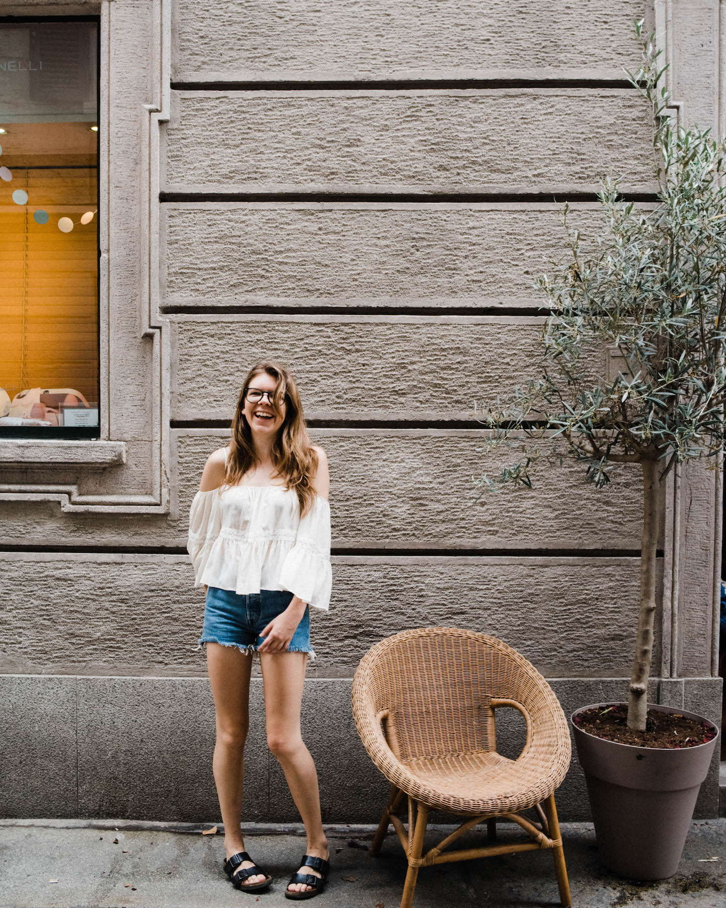 Wide portrait photo of a Rhianna May, an Italian Destination Wedding Photographer, smiling and standing in front of a typical Milanese facade in Brera.