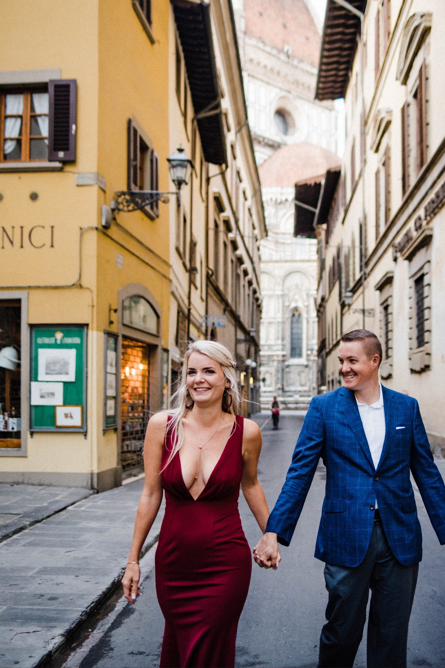 A couple walk hand-in-hand down a laneway in florence, laughing and smiling. She wears a red dress and he wears a blue suit.