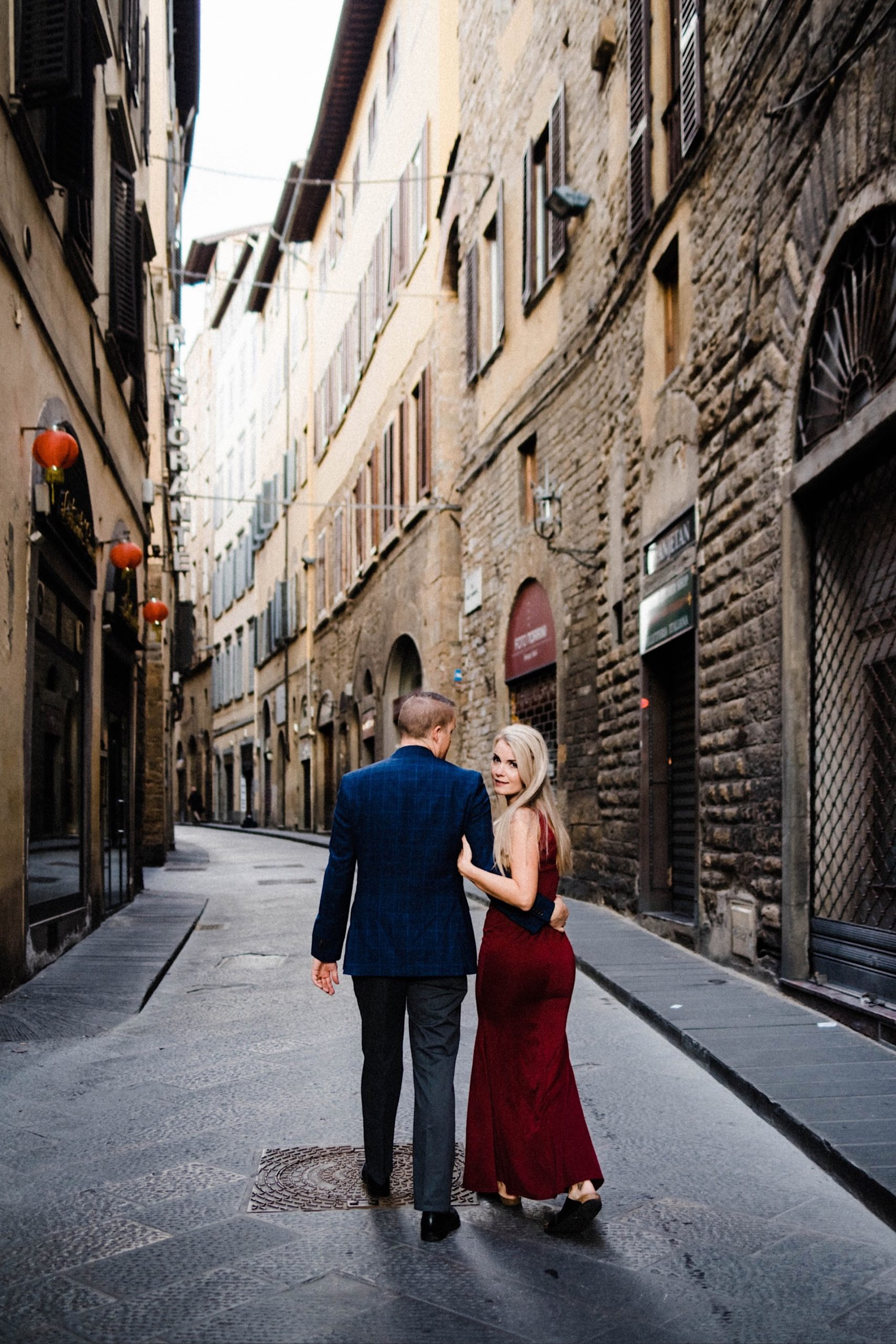A wide, portrait photo of a couple walking down a curved laneway in Florence. He looks at her, and has his back to the camera, and she looks back at the camera.