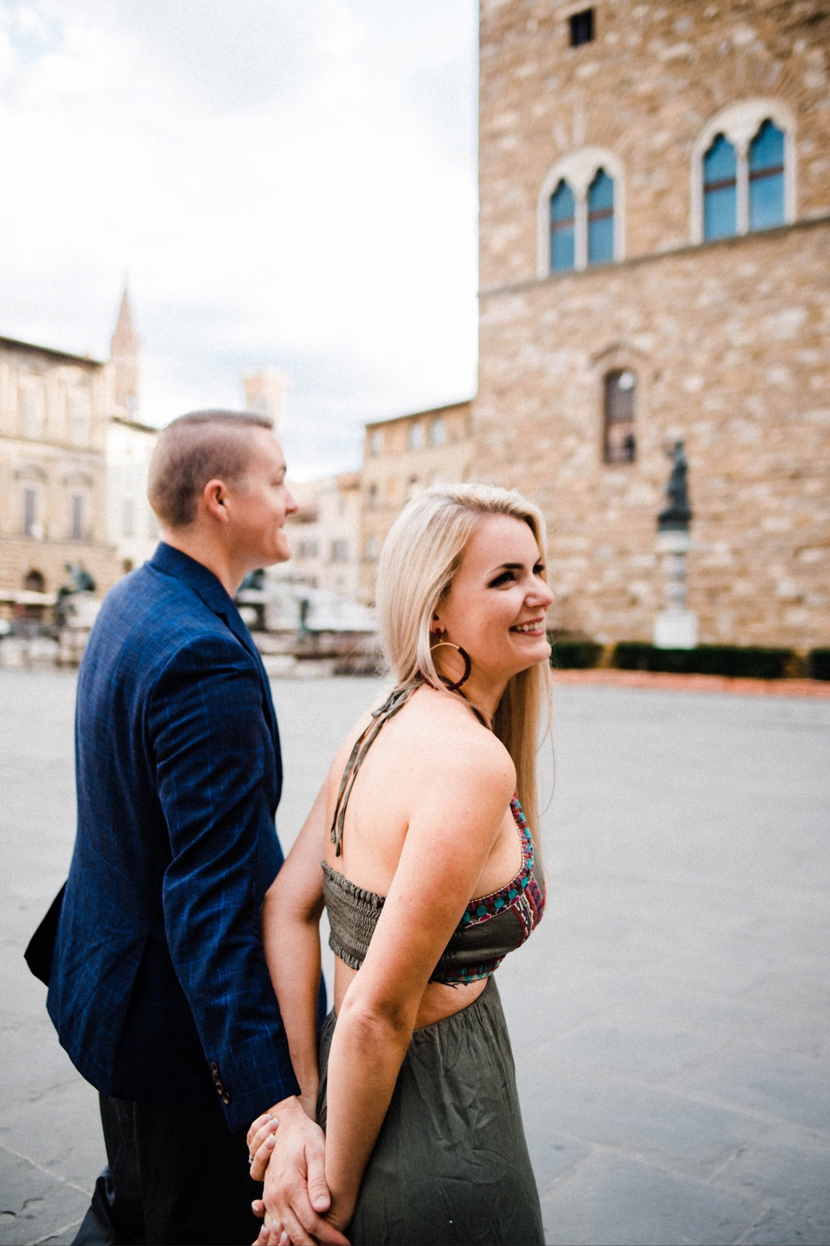 A candid portrait photo of a couple walking through the Piazza della Signoria in Florence, holding hands and laughing.