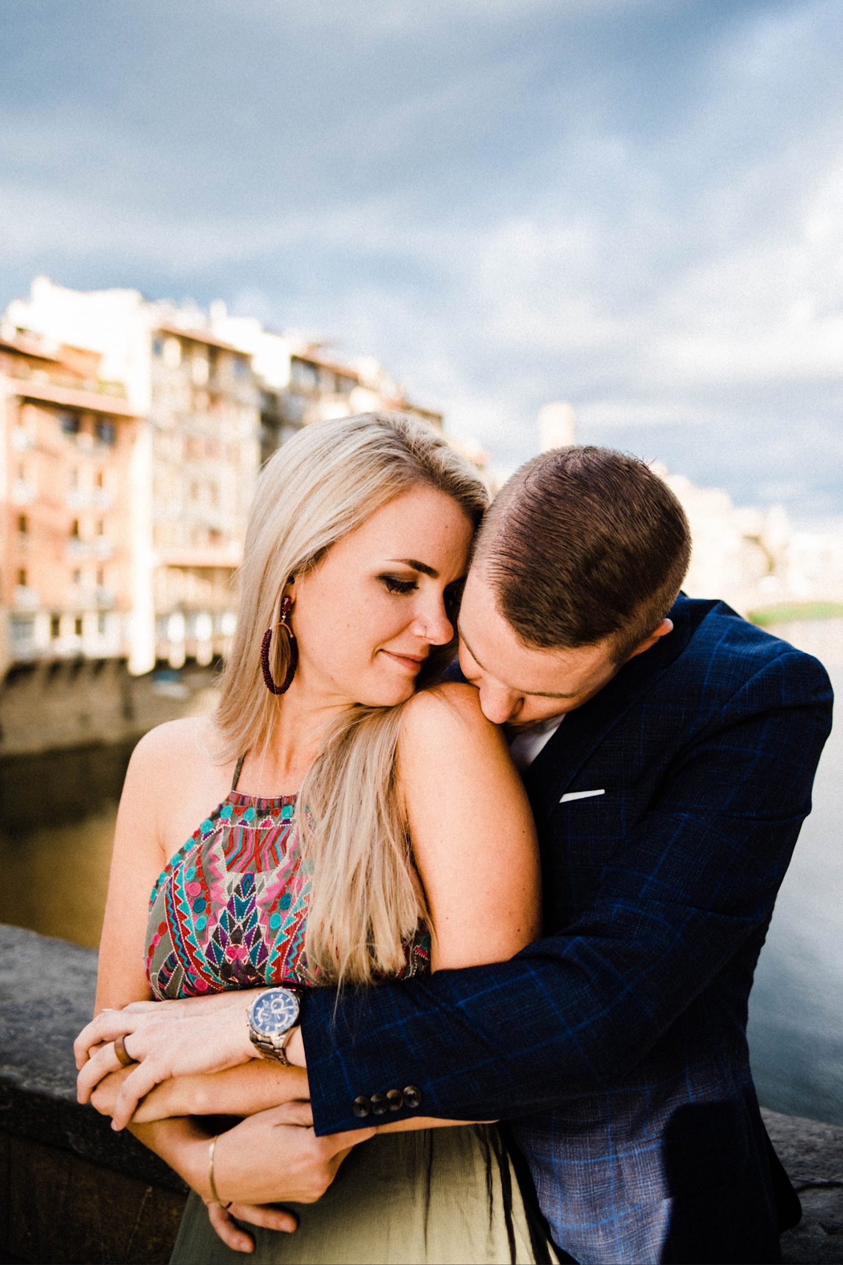 A couple shares an intimate moment, cuddling and holding hands, on the Ponte Vecchio in Florence.