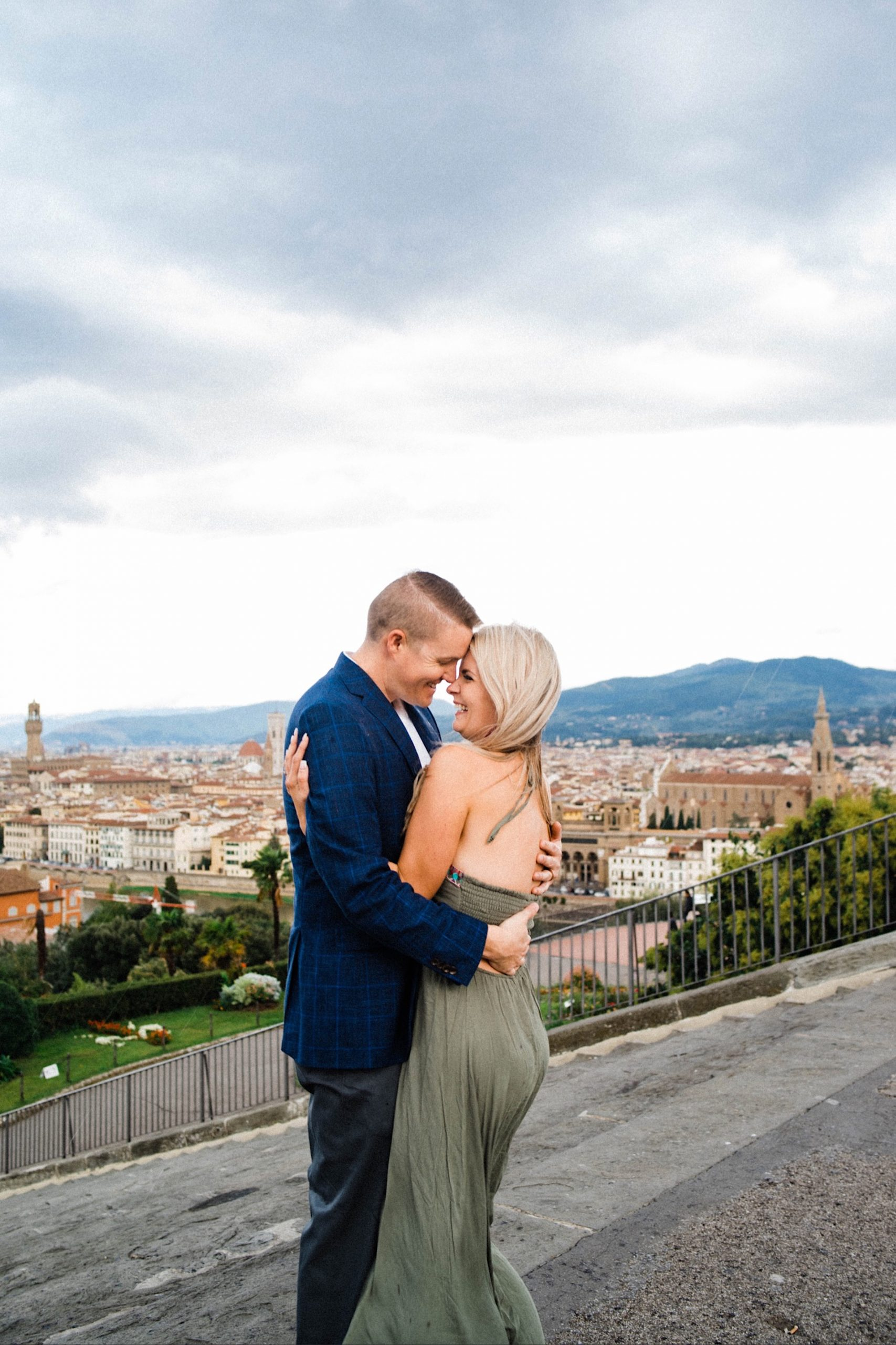 Florence Anniversary Photography featuring a couple standing in the Piazzale Michelangelo, with Florence in the background, as they hug and laugh.