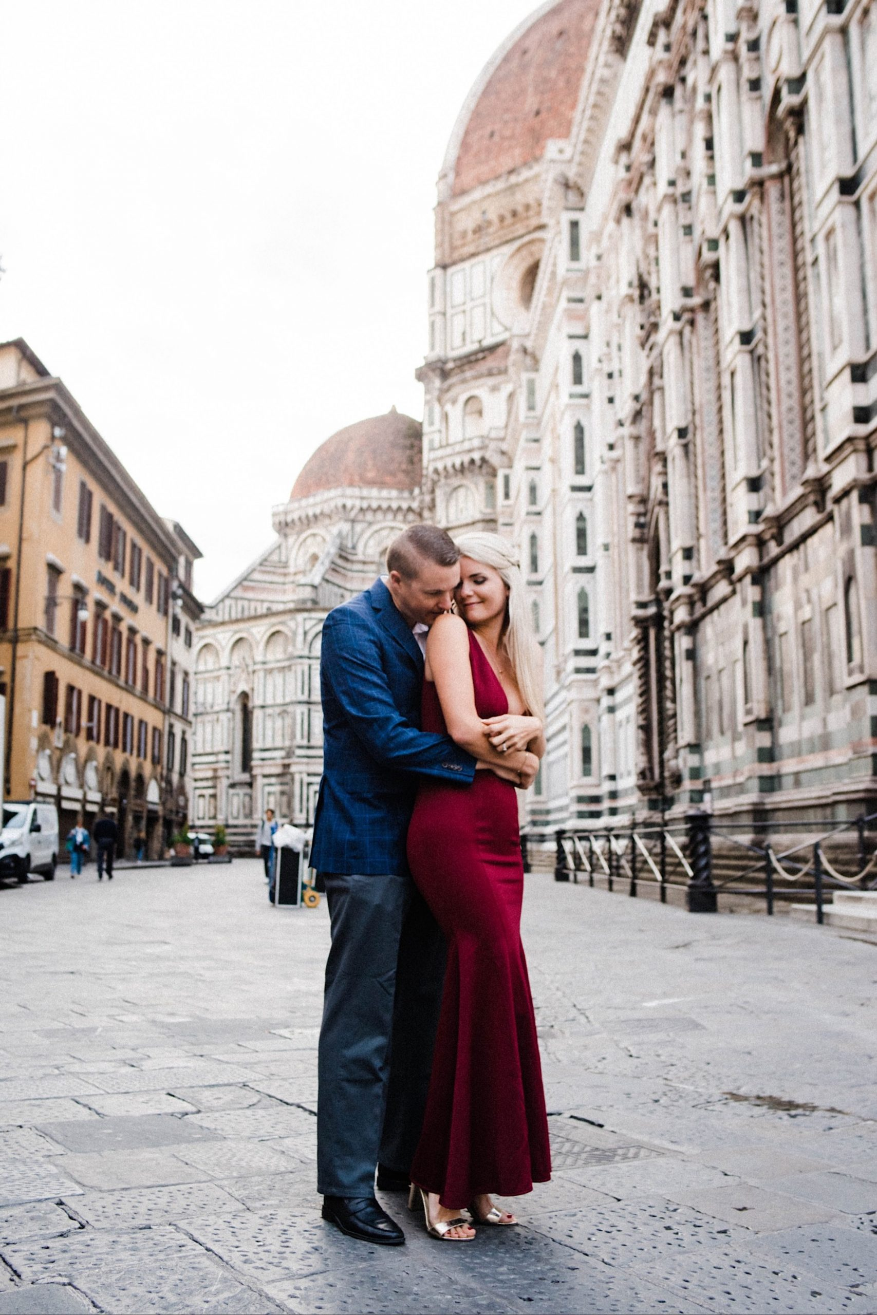 A wide shot, taken from a slightly low angle, looking up at a couple embracing in front of the Duomo di Firenze during their Anniversary Portraits.