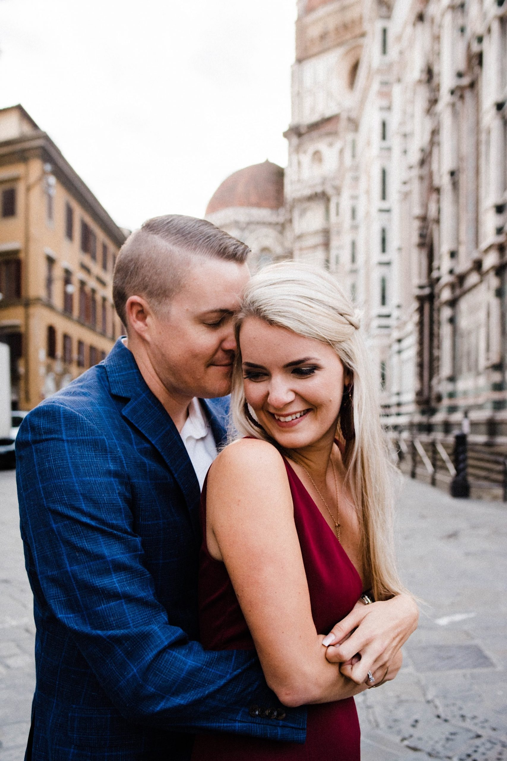 A close up of a couple embracing in front of Florence's Duomo.
