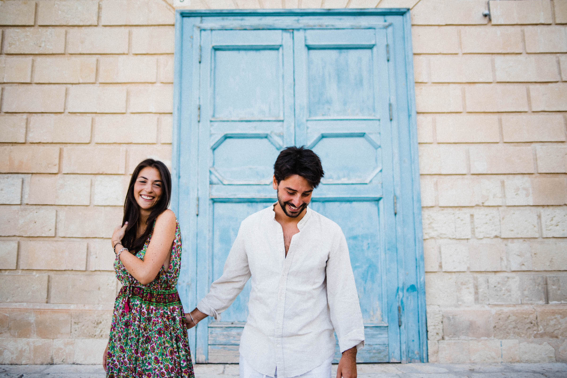 Italian Wedding Photographer's work of a couple during their Sicily Couples Photography session at Noto, standing in front of a blue door and laughing.