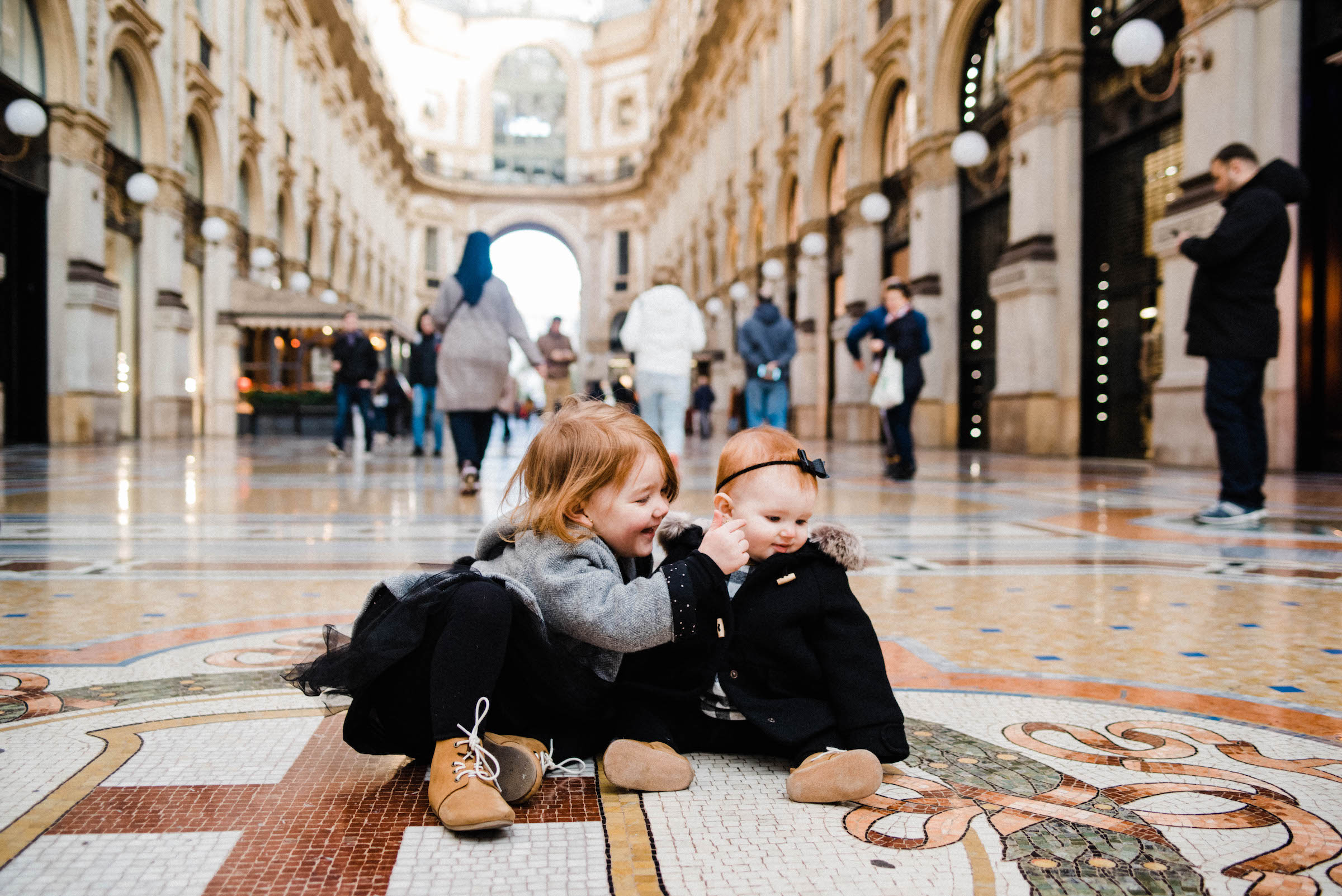 Italian Family Photographer's work featuring two little girls, who are sisters, sitting in the Galleria Vittorio Emanuele in Milan during their Family Portrait Session.